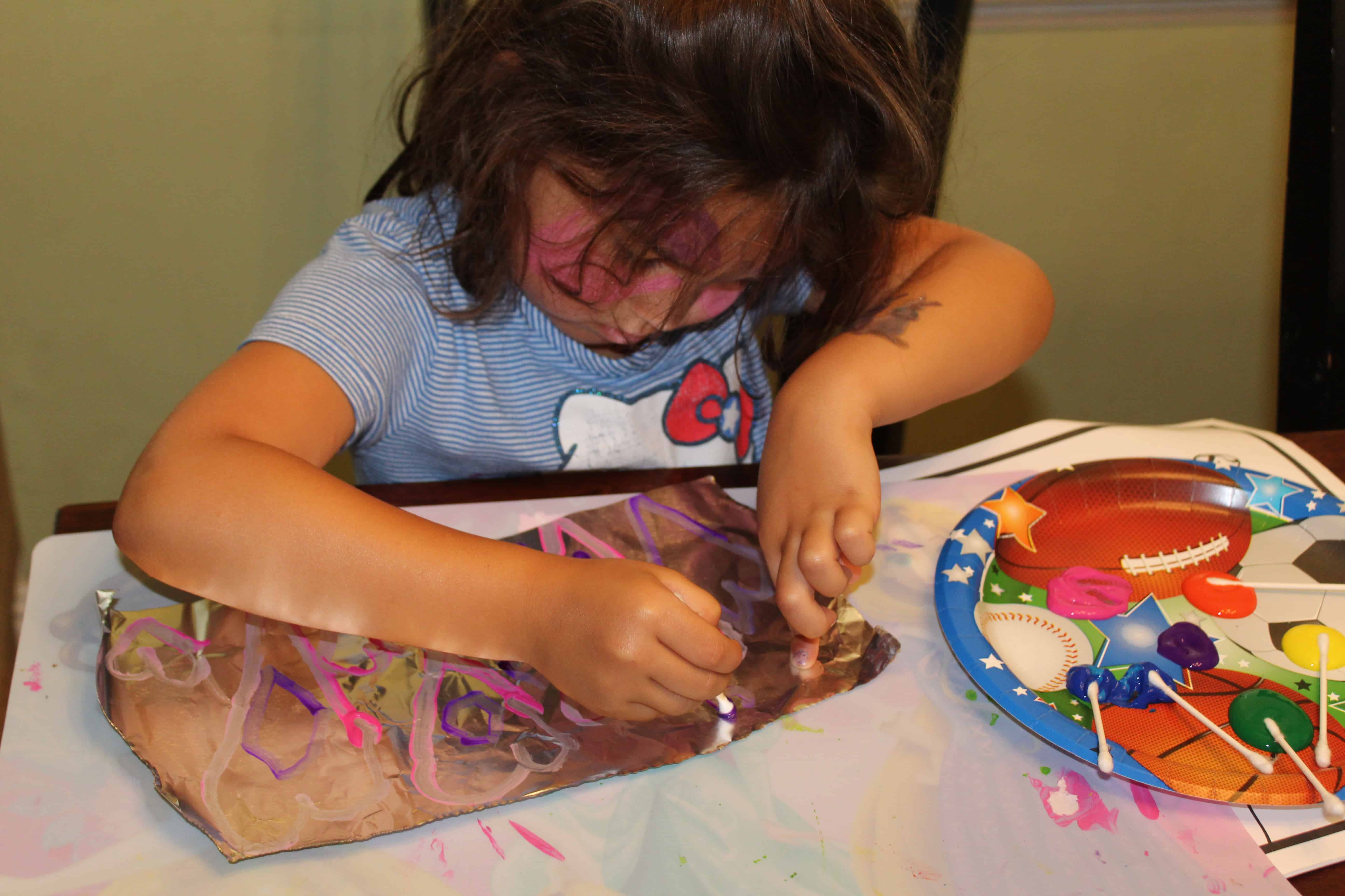 A child painting a sheet of foil with paints using cotton swabs.