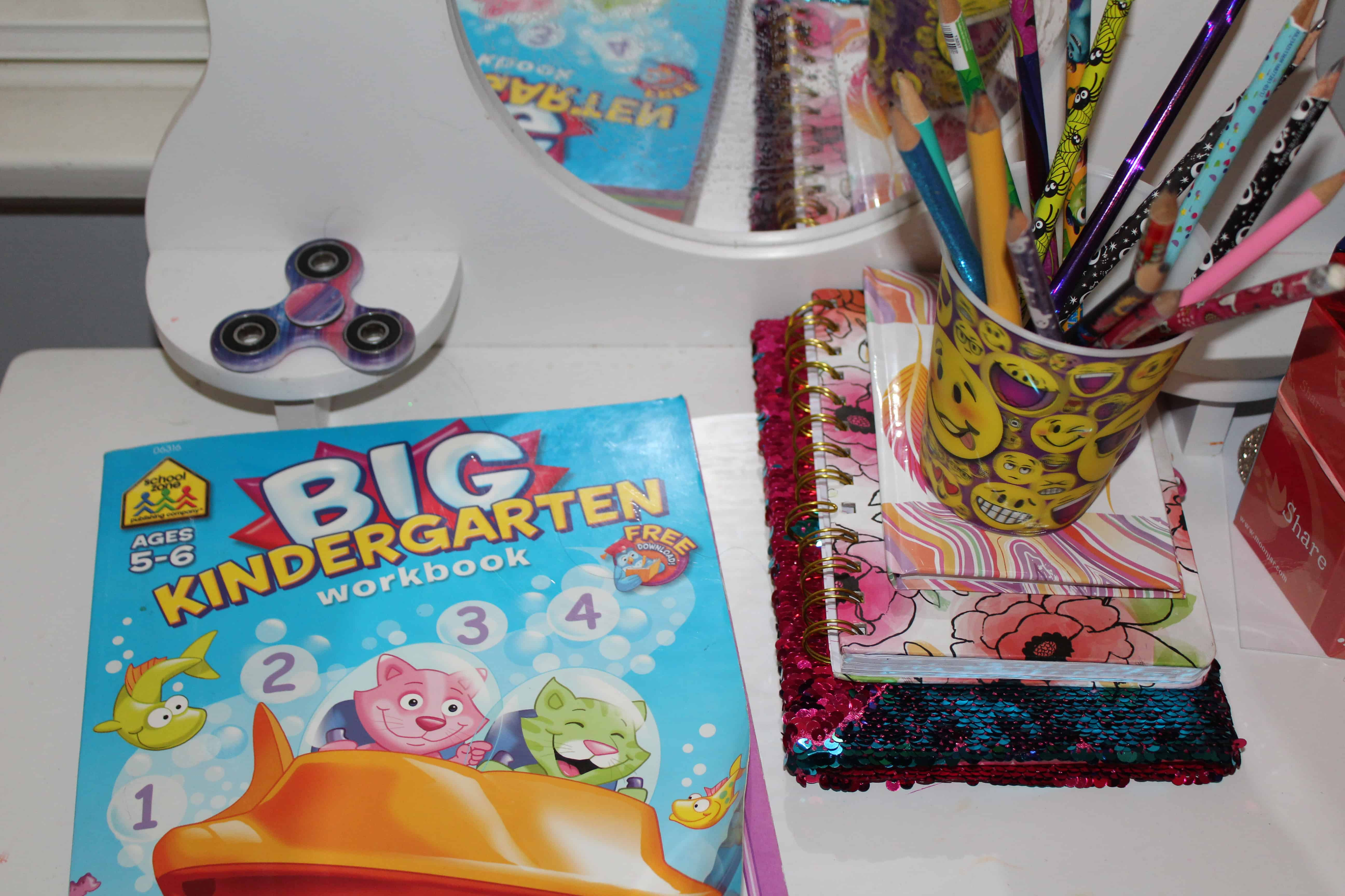 Big Kindergarten workbook for toddles next to a cup of pencils and fidget spinner