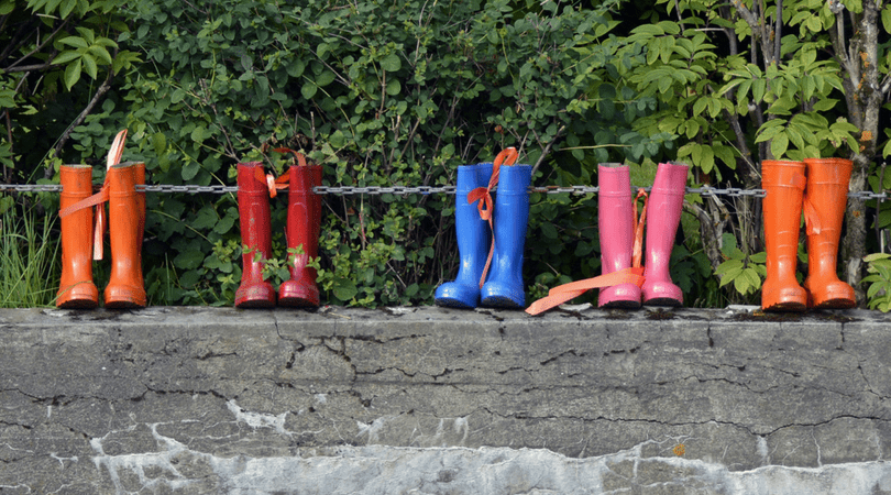 5 Pairs of rain boots all different colors on a stone wall.