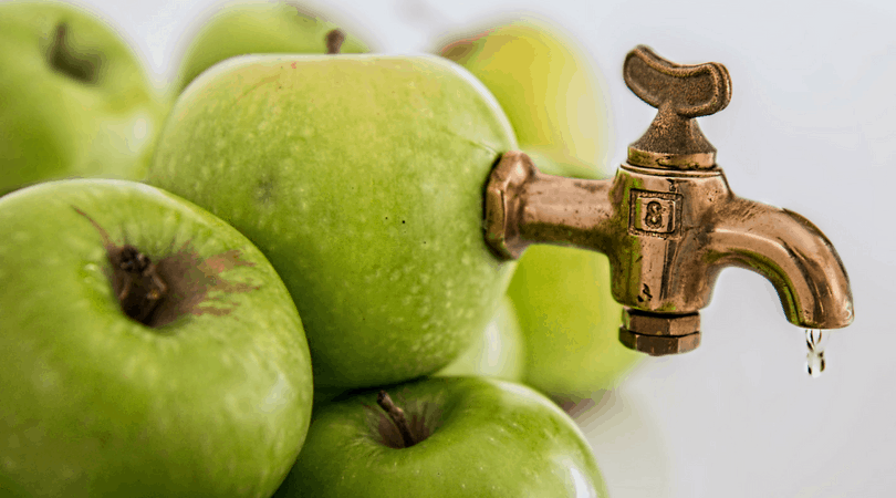 A pile of green apples one apple at the top has a brass faucet sticking out of it with a trickle of liquid coming out.