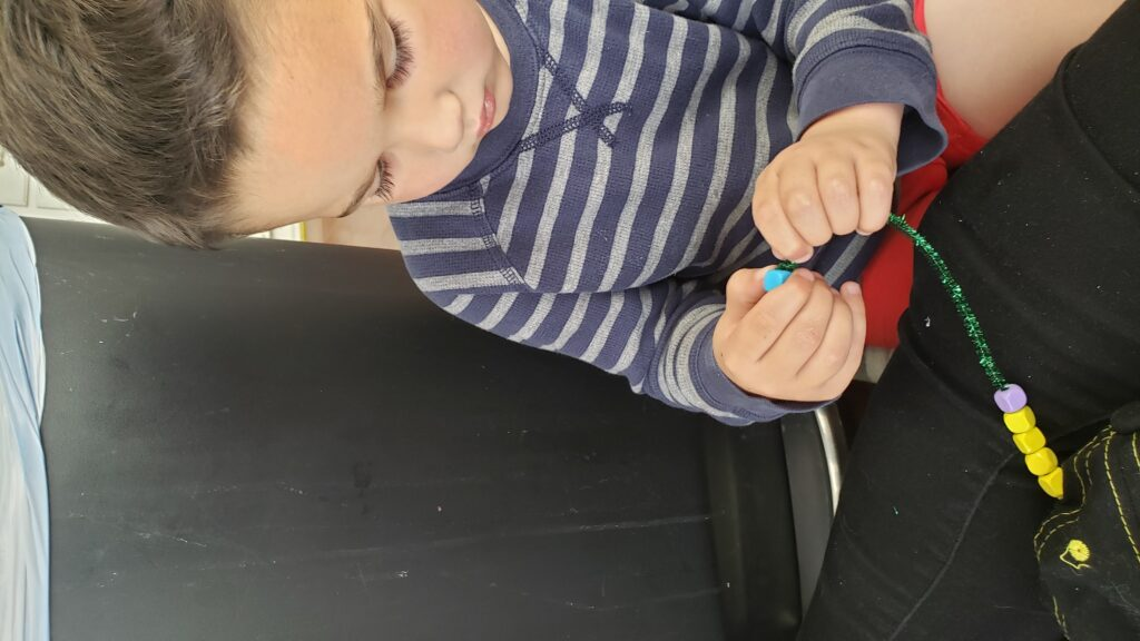 child putting beads on a pipe cleaner
