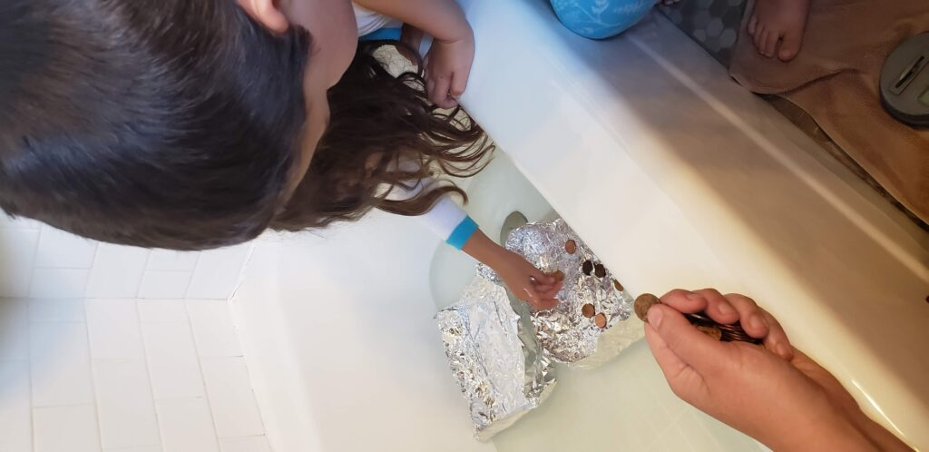 kids making boats with tin foil