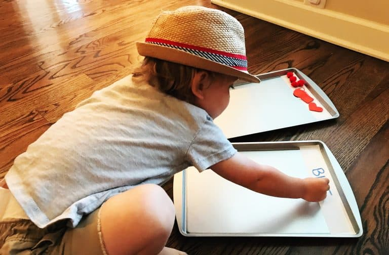 Baking sheets with magnets while a child sorts.
