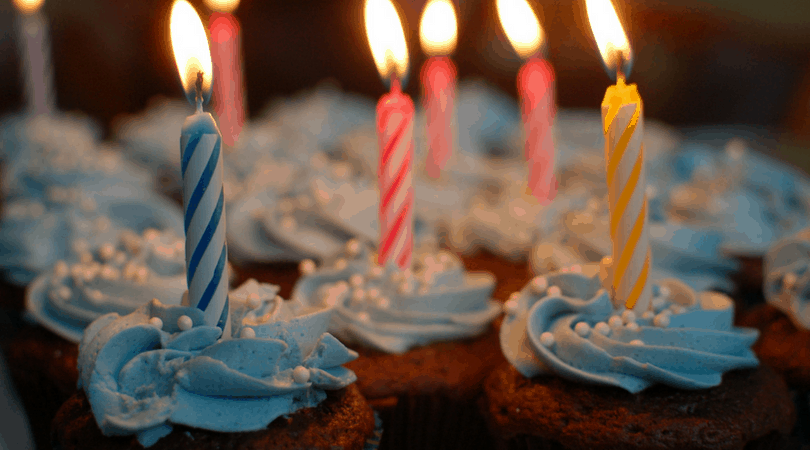 Chocolate cupcakes with blue icing and lit candles.