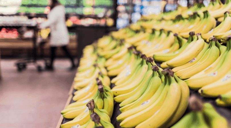 Banana's in the aisle of a grocery store