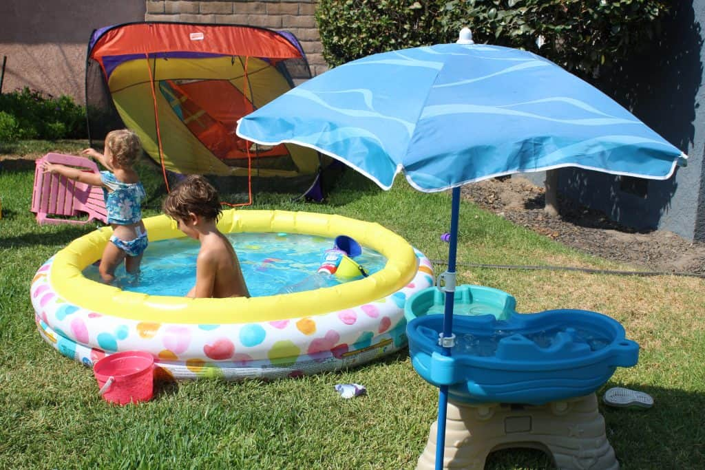 young toddler and preschooler in an inflatable kiddy pool