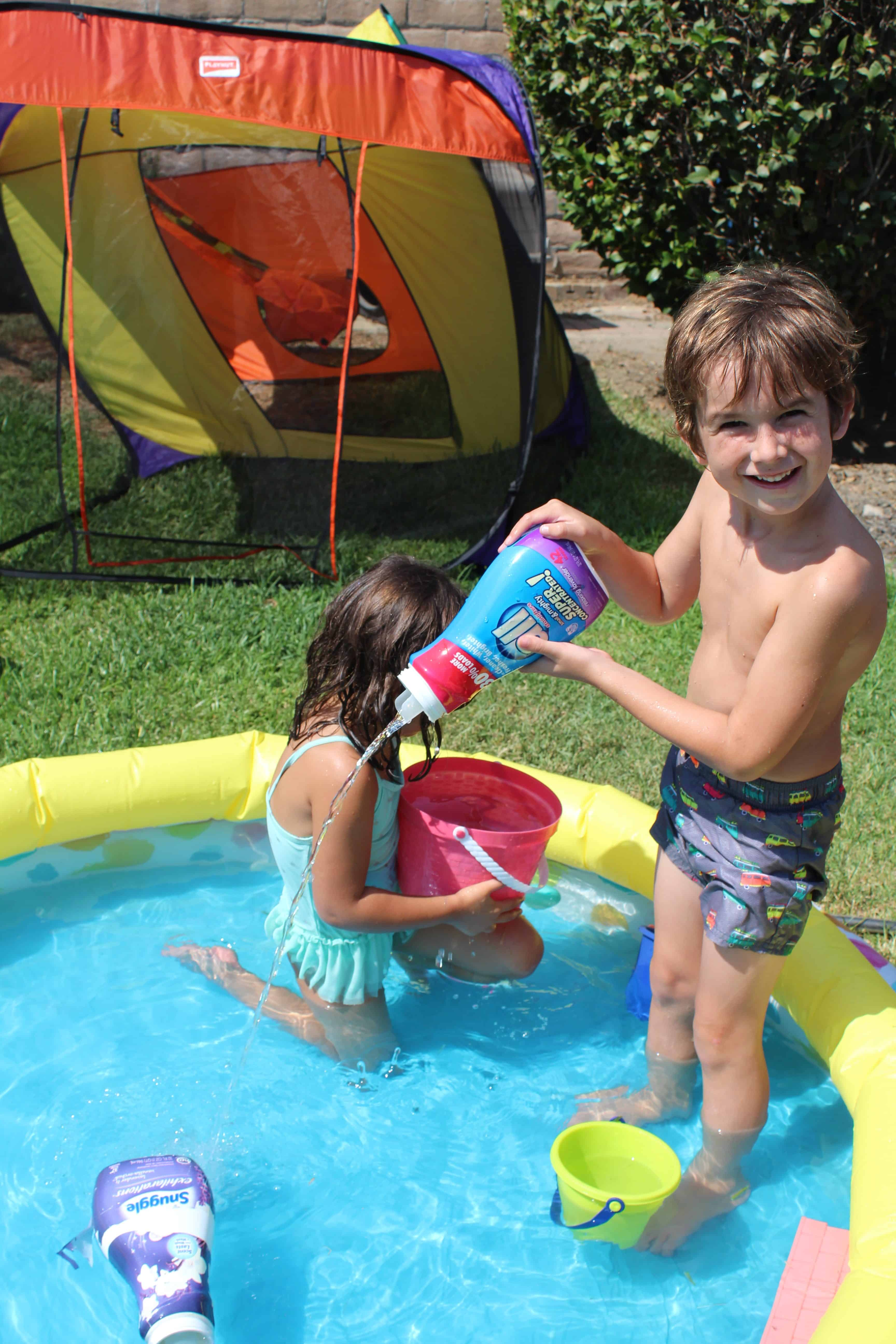 Two young children playing in an inflatable kiddy pool using an old laundry detergent bottle to pour water into the pool.
