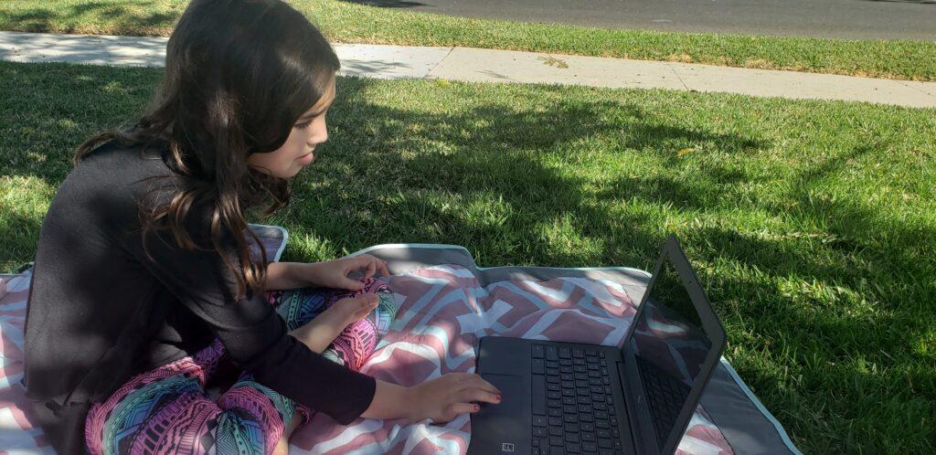 child doing their homework outside