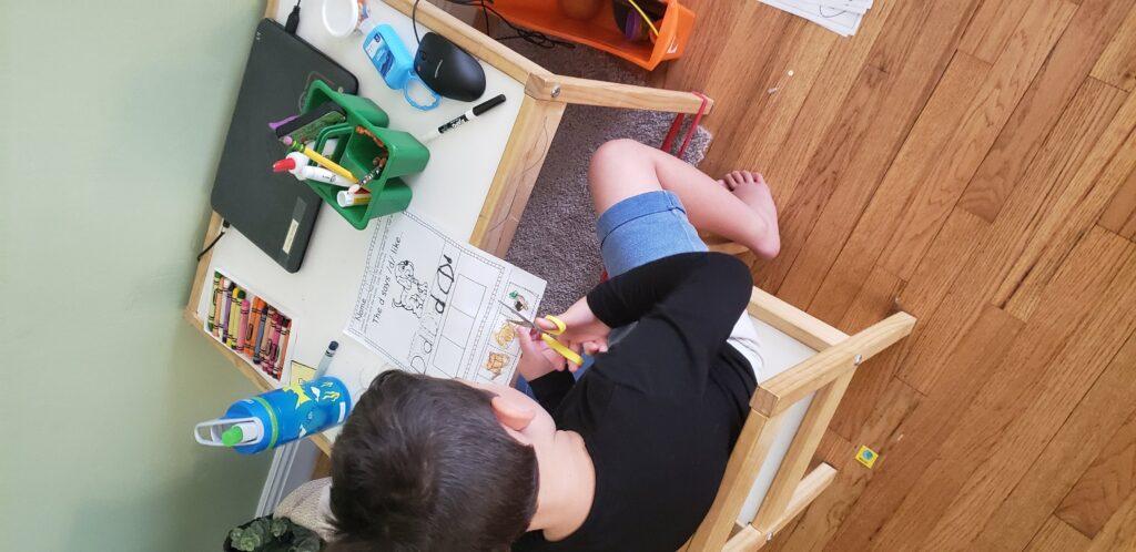 preschooler cutting a worksheet
