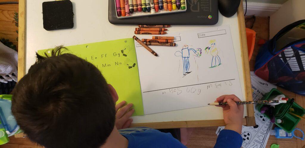 kindergarterner writing in their journal