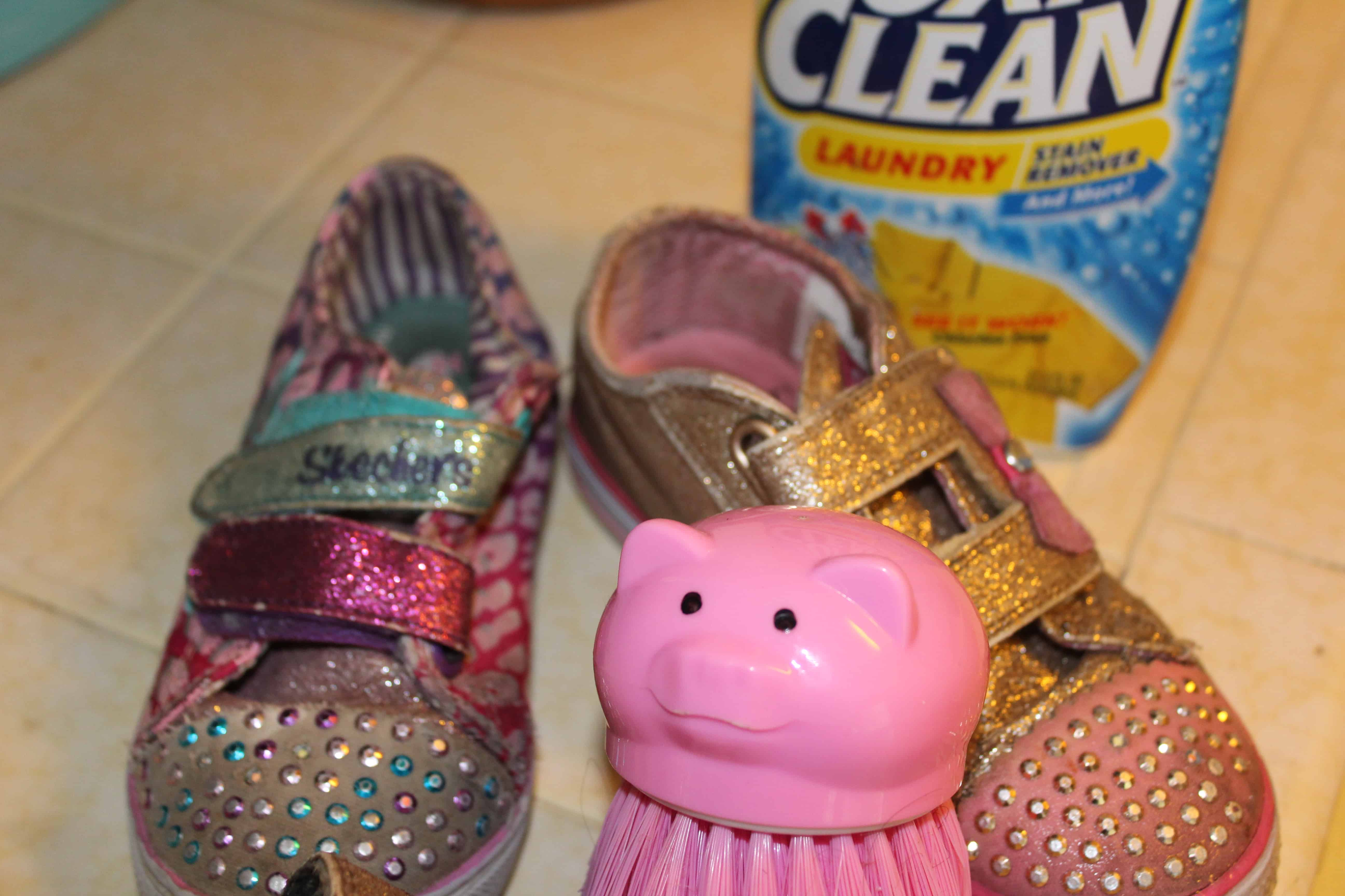 A pair of dirty shoes sitting next to a pig shaped scrub brush with a bottle of Oxiclean in the back ground