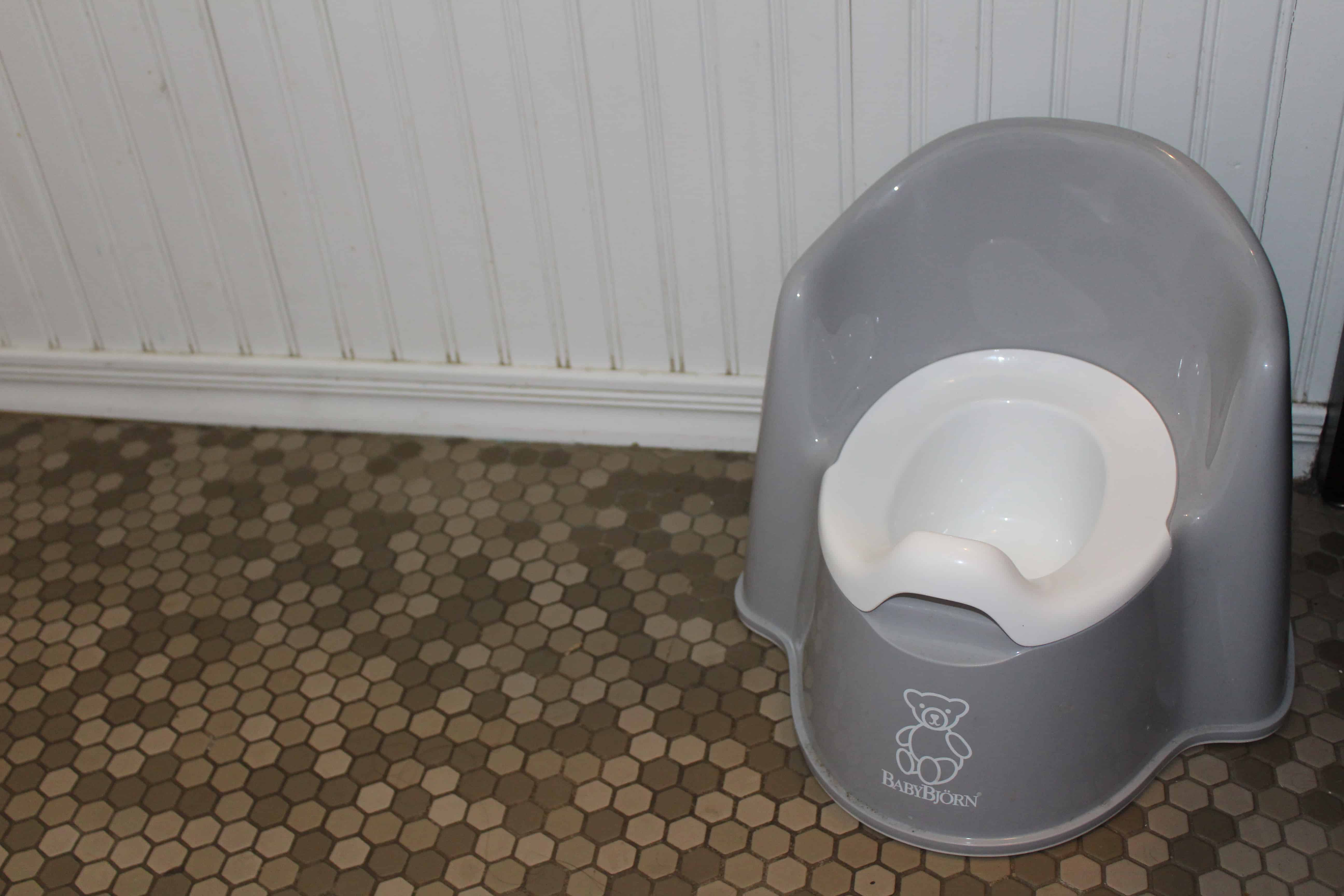 Gray toddler potty training seat in the corner on tile.