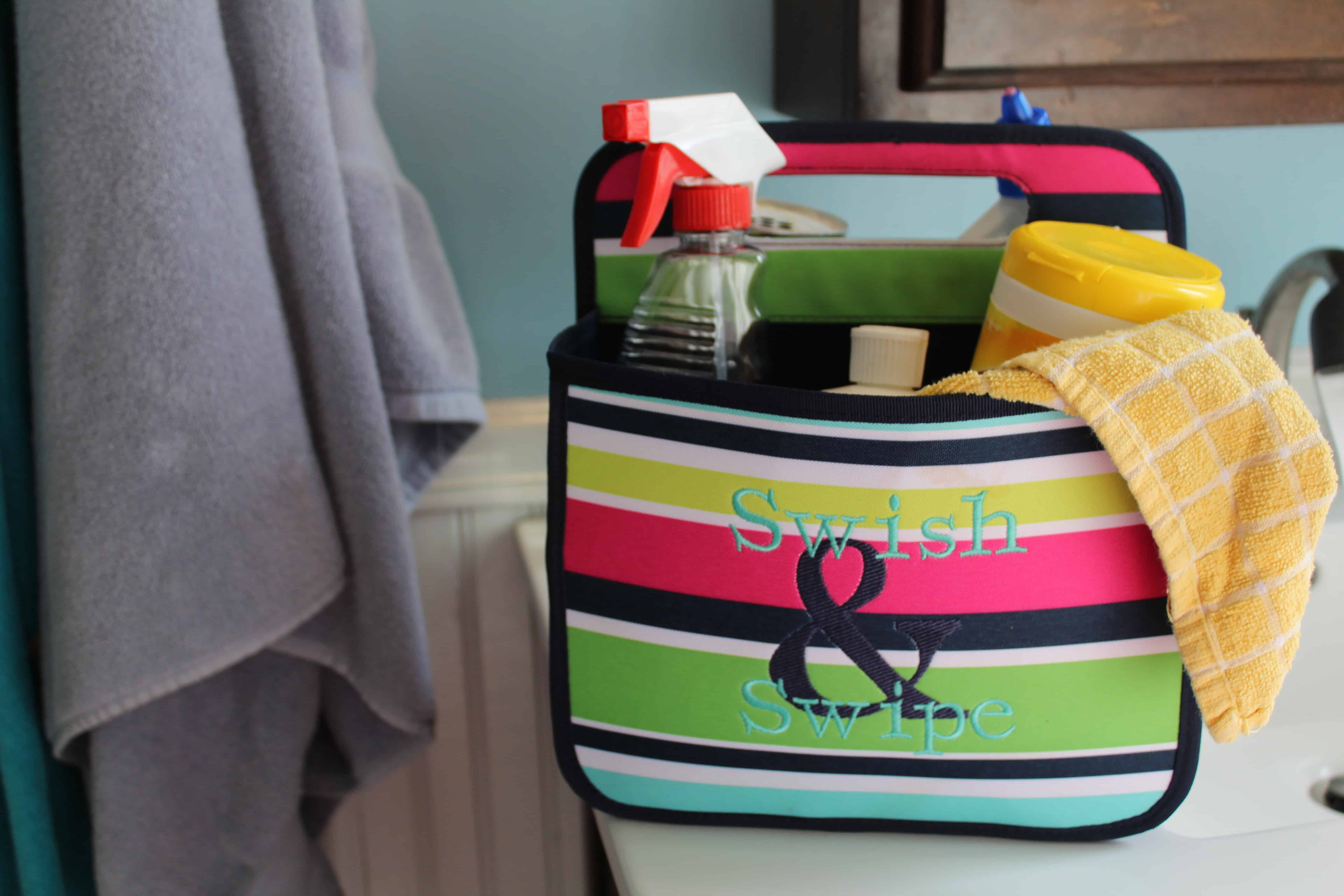 """31 Bathroom caddy bag with various chemical cleaners and cleaning rag inside of it. """"Swish & swipe"""" is embroidered on it."""