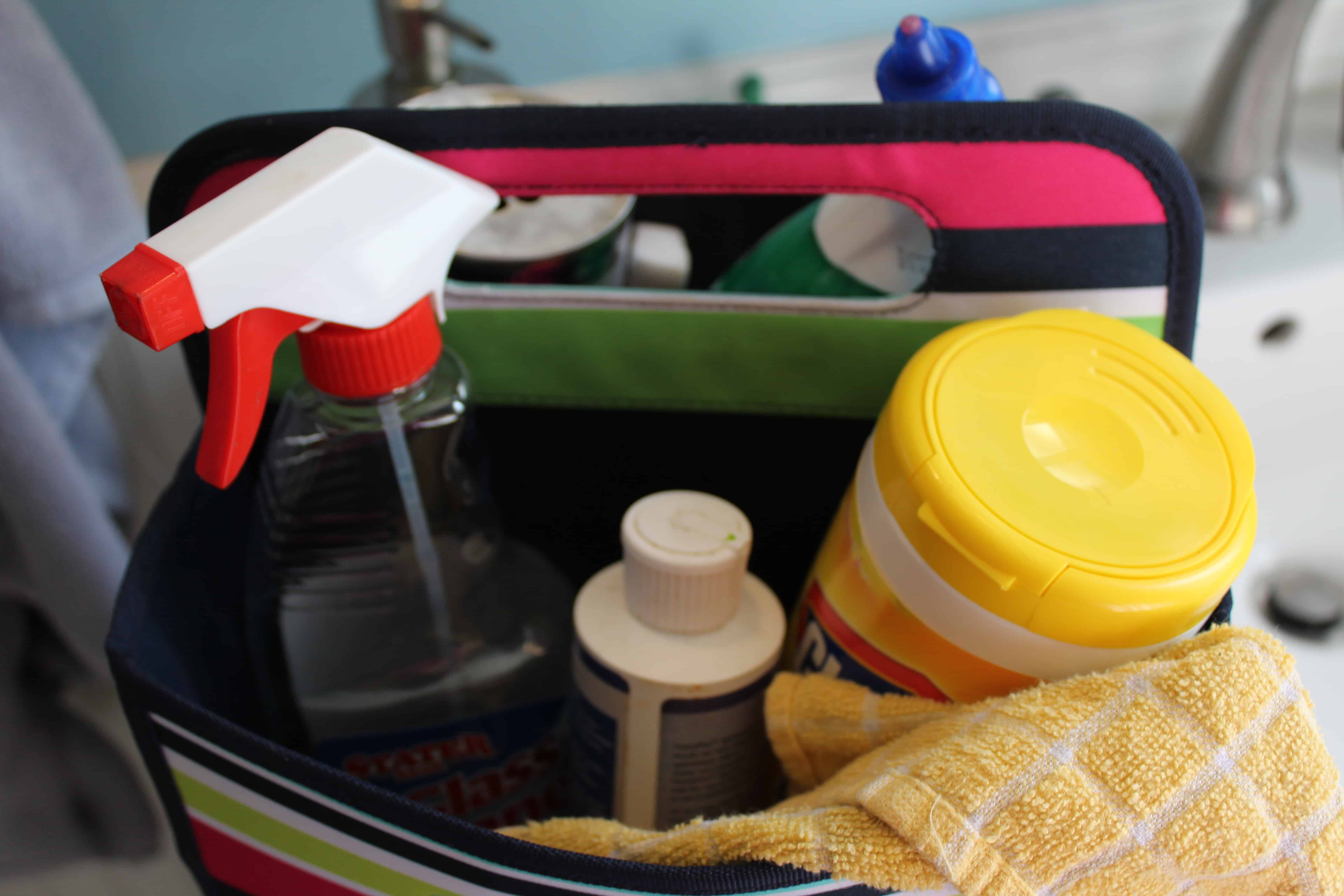 A picture of inside the bathroom caddy bag. A bottle of glass cleaner and a container of clorox wipes are inside with other cleaners and a yellow cleaning rag.