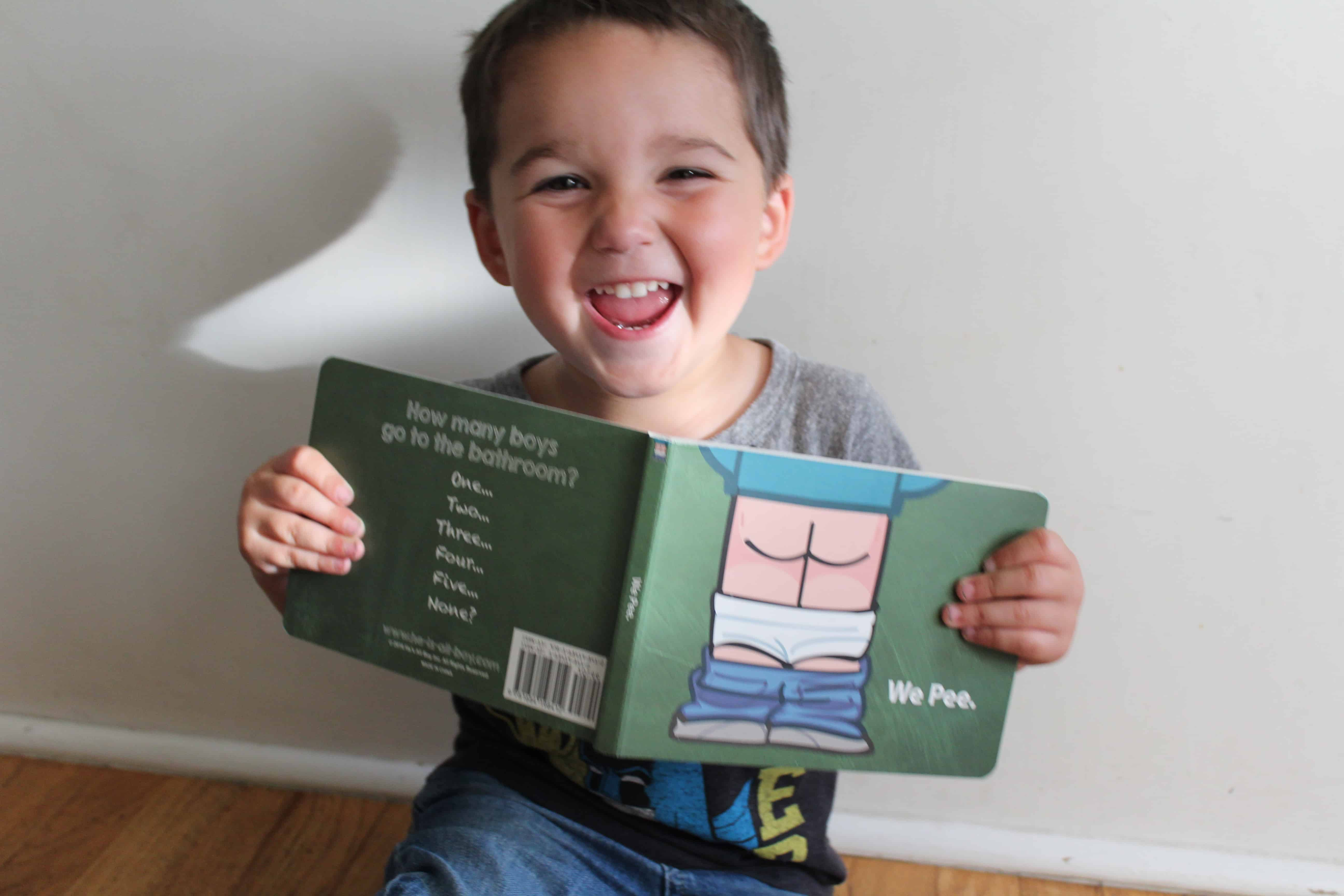"""Smiling toddler boy holding the book called """"We pee"""""""