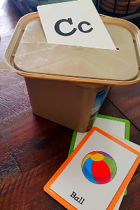 card being dropped through a slit in a butter container lid