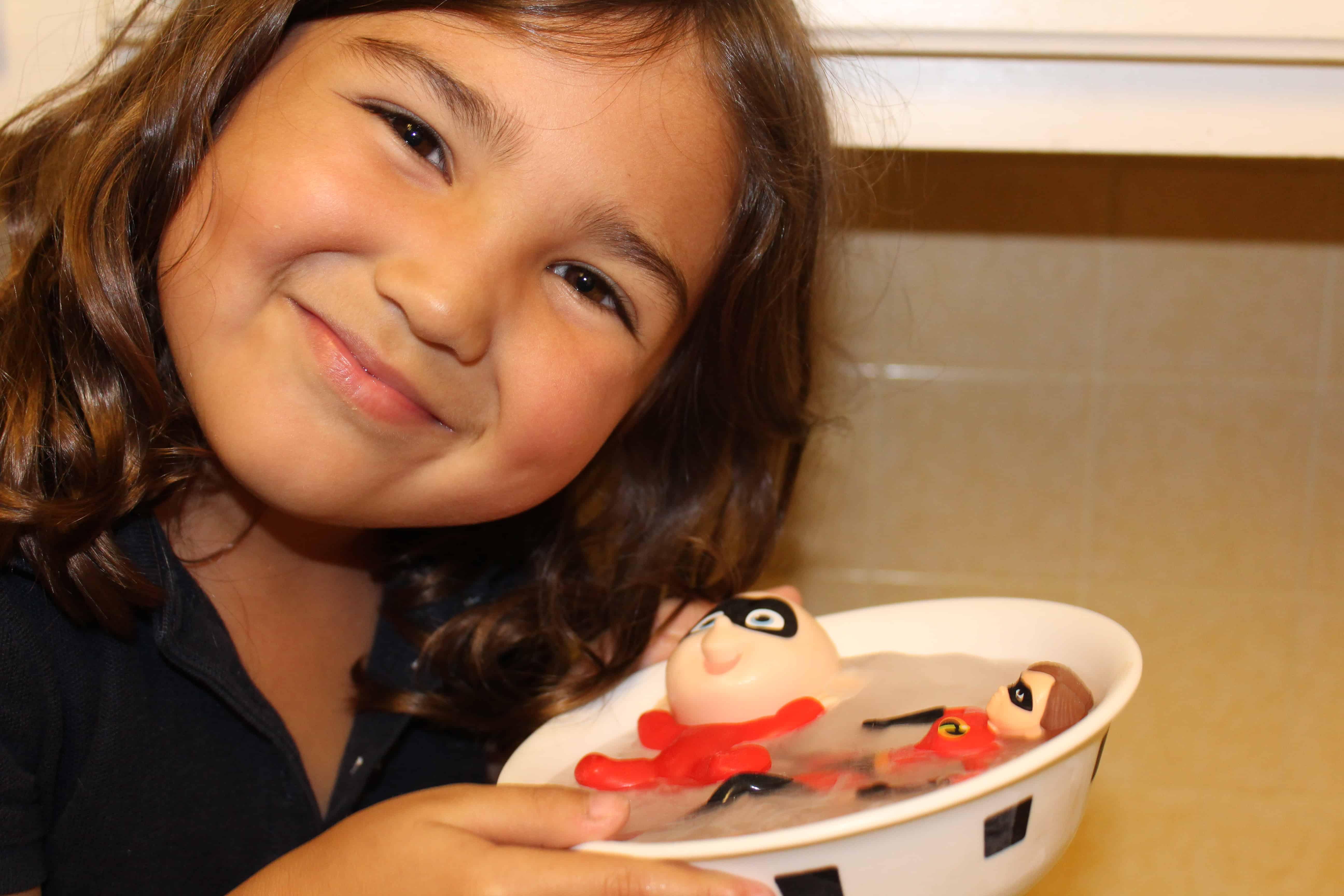 Smiling girl holding bowl of frozen ice.