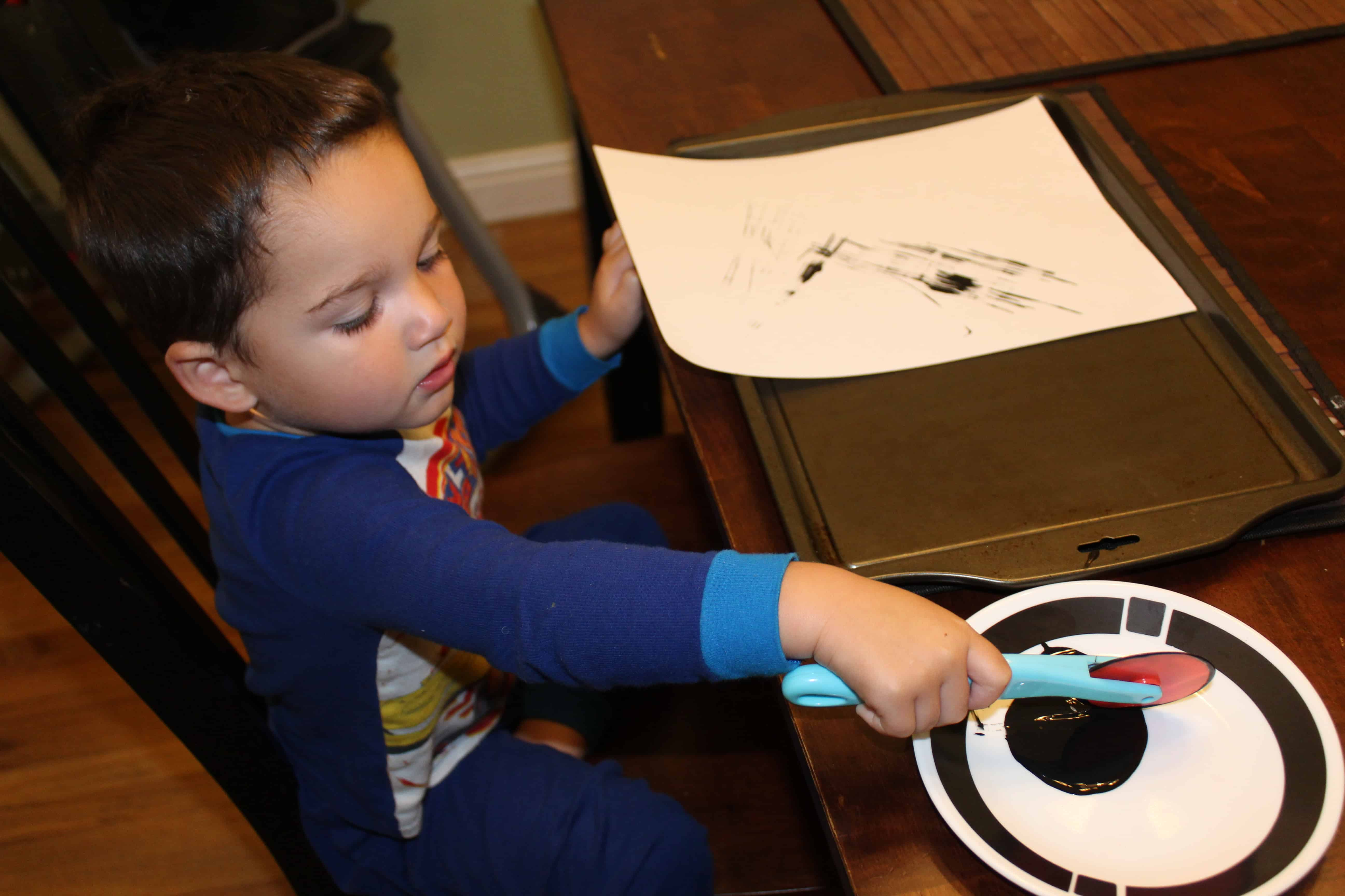 A bit of black paint on a plate toddler using playdough tool to paint