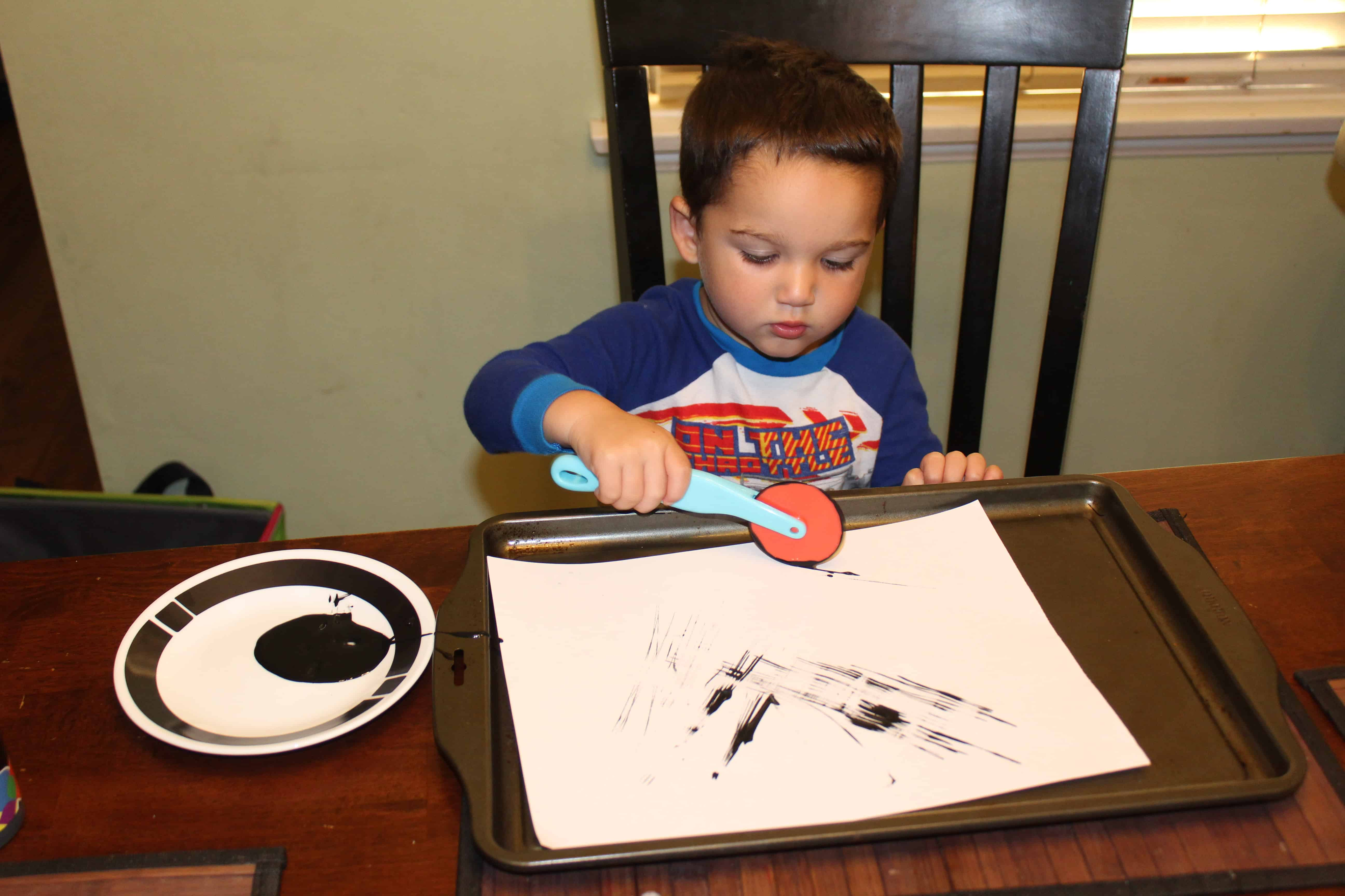 Toddler using play dough tool to paint lines on the white sheet of paper.