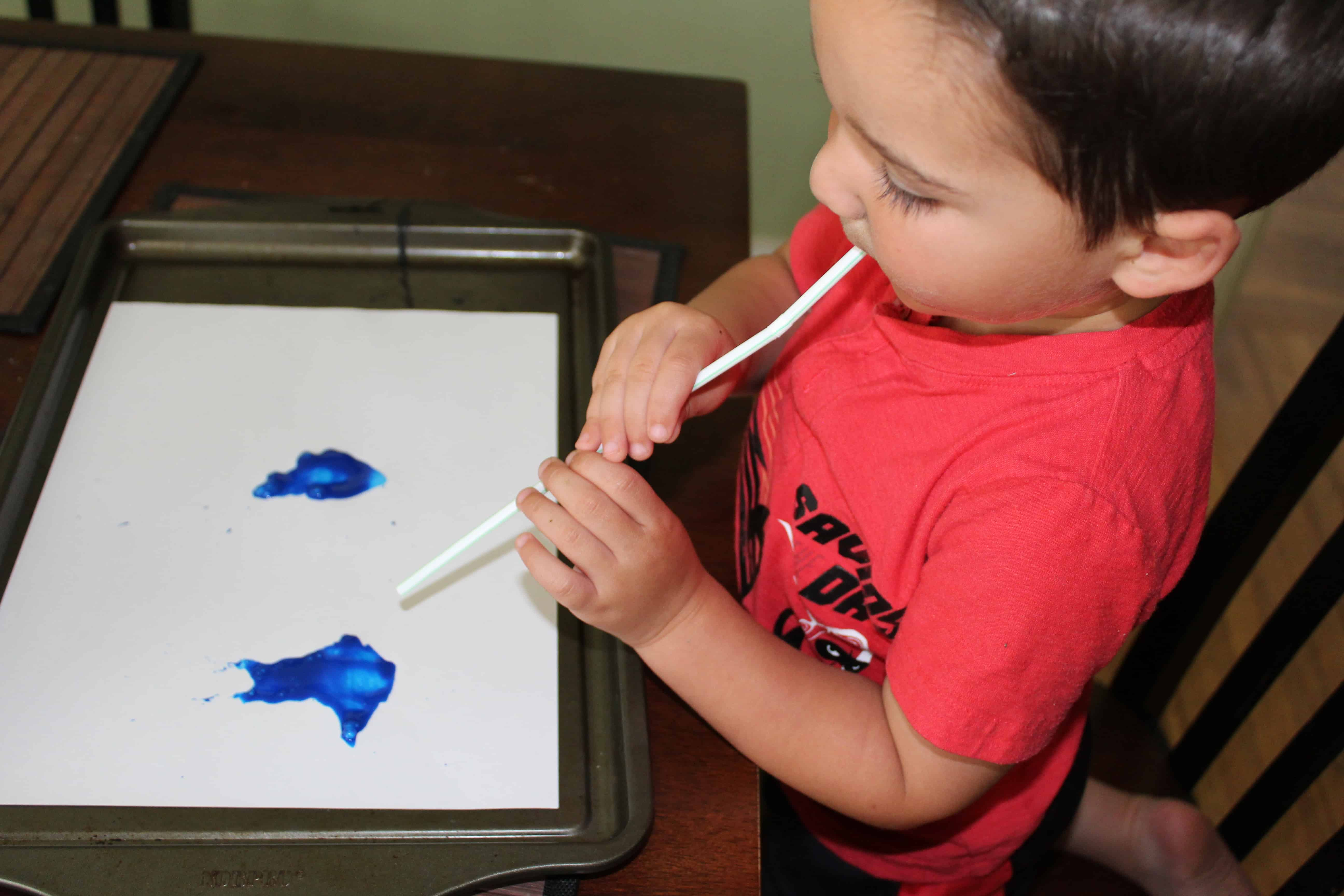 Toddler blowing pain patterns on a white sheet of paper.