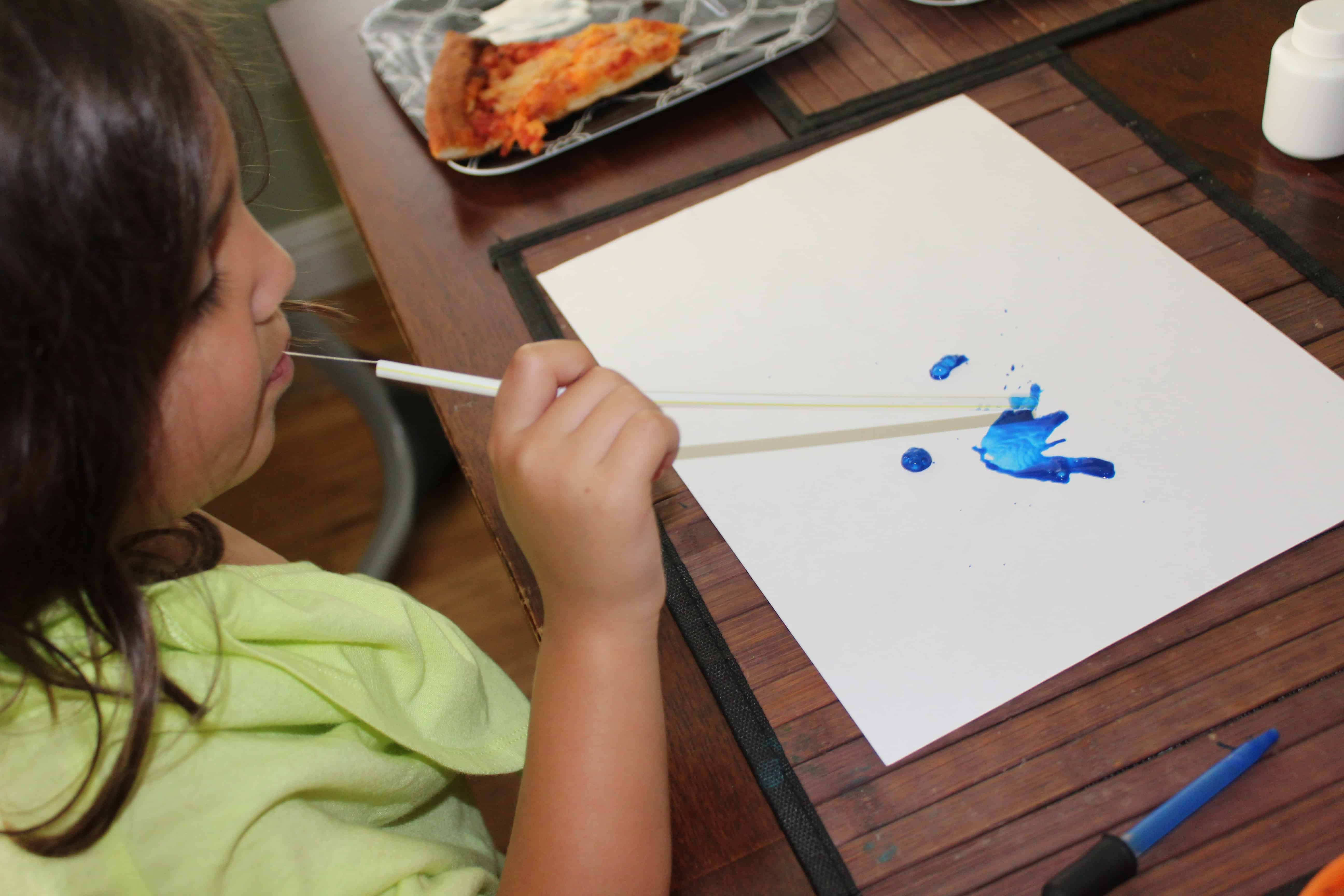 Little Girl using straw to blow paint patterns on a white sheet of paper.