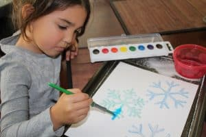 Create snowflakes with this winter process art project featuring Raised Salt Painting. With simple materials and great results, this snowflake art project will be one kids want to repeat again and again. Get the instructions at TheSaltyMamas.com. #snowflake #snowflakeart #winter #wintercrafts #winterart #snowtheme #preschoolsnowtheme #preschoolwintertheme #processart #processartforkids #kidsart