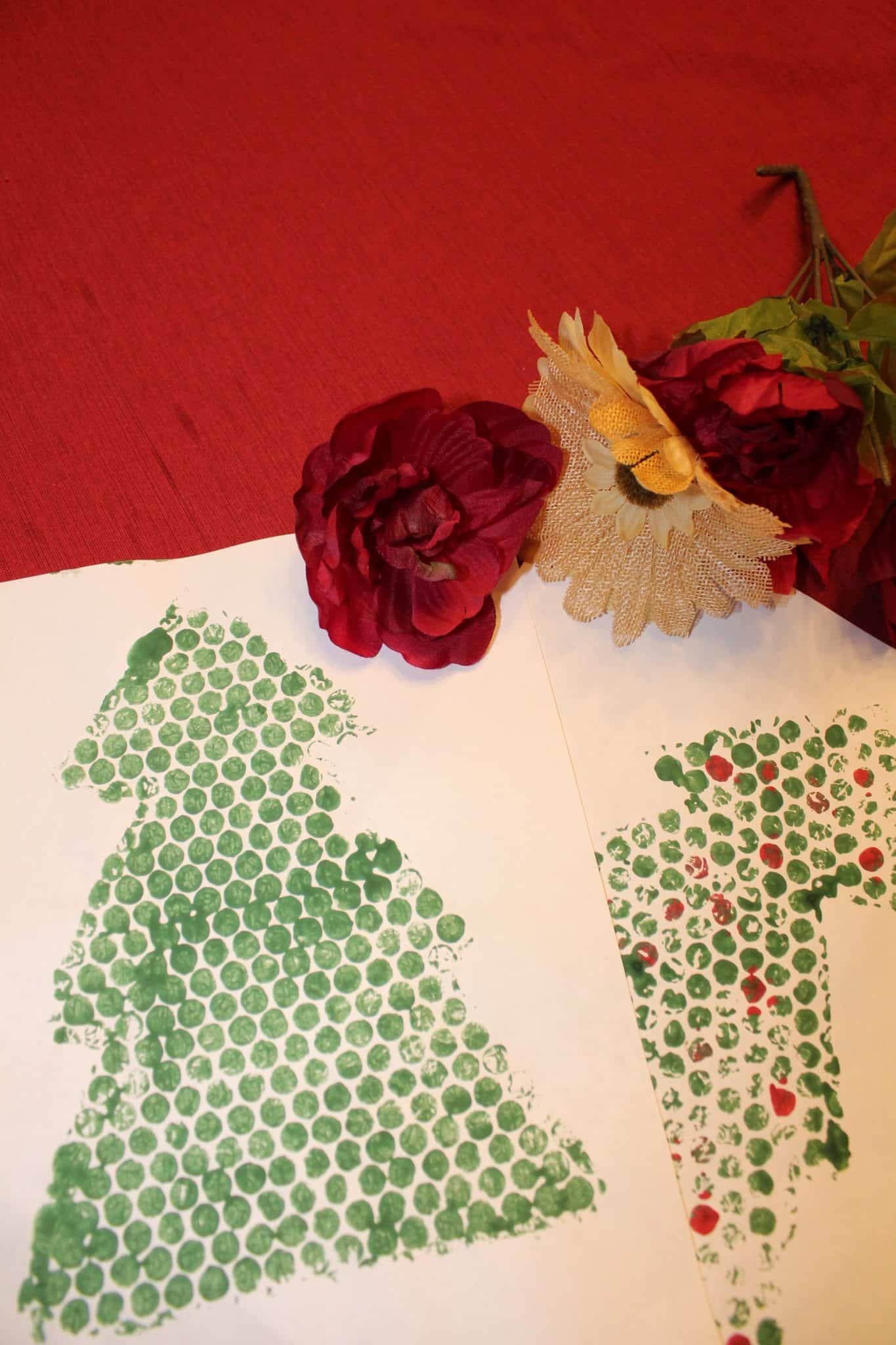 White paper with green painted outline of a Christmas tree.