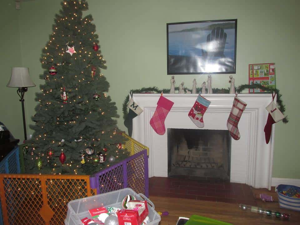 A Christmas tree with a gate around it, along with a Fireplace with stockings hung safely on the mantle.