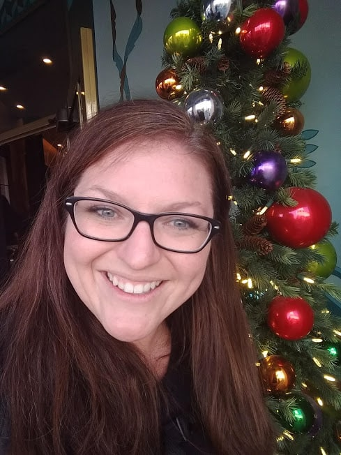 Smiling lady in front of shiny Christmas tree.