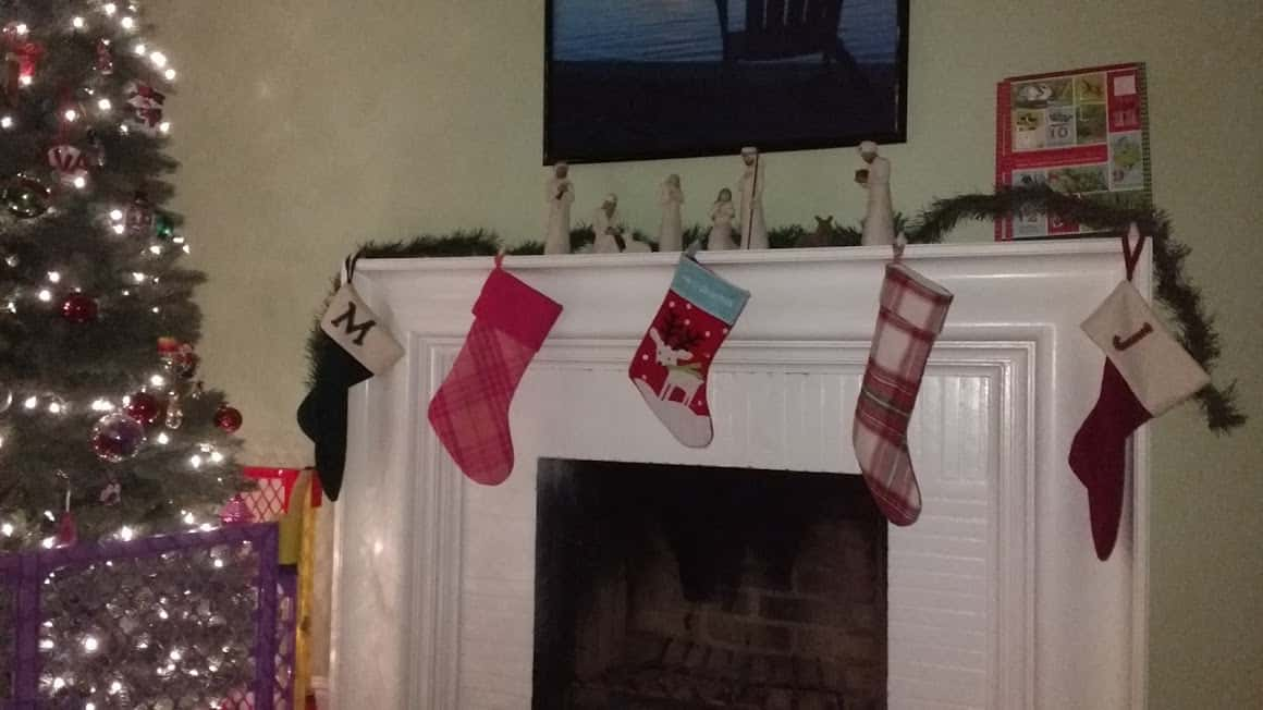 Four Christmas stockings hanging safely from the top of the mantle of the fire place.