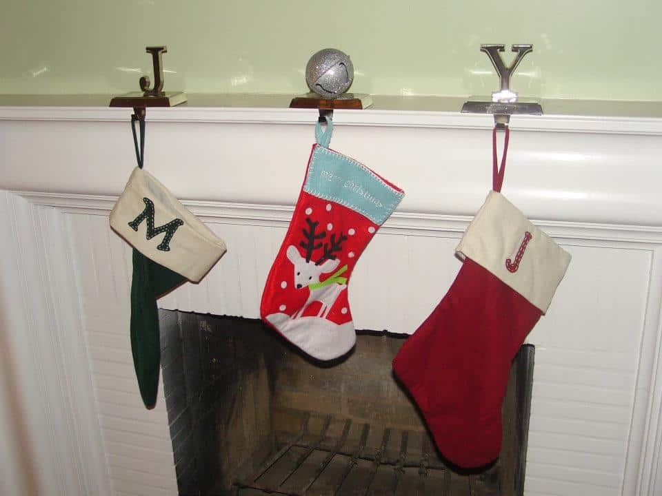 Three stockings hanging in front of the fire play with hangers spelling out JOY