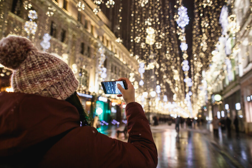 Outdoor night portrait of young fashionable woman in the winter hat with pompom taking photo by phone rear view. Magic snowfall effect. Night street illumination in Moscow.