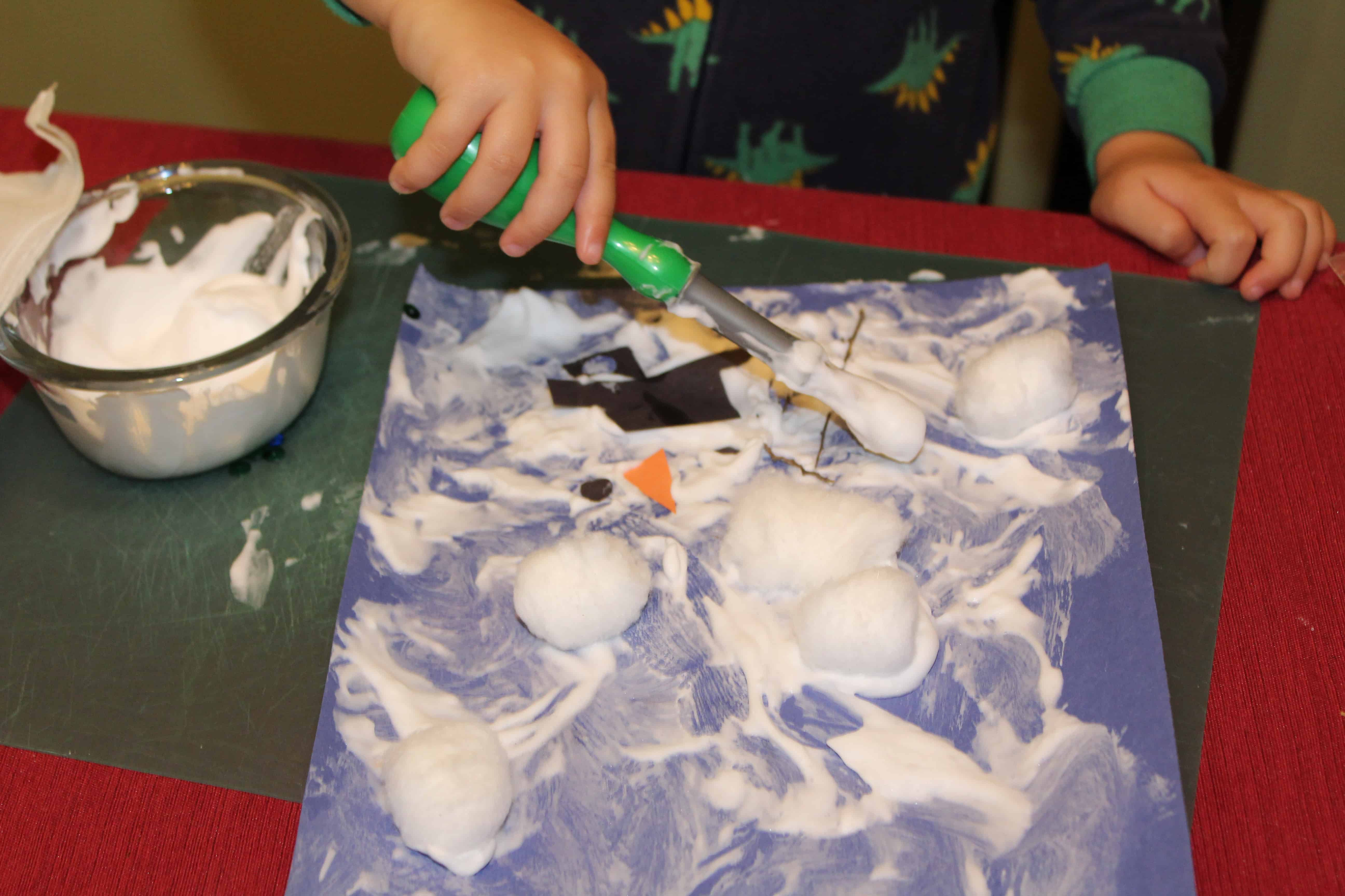 toddler painting snowman with shaving cream