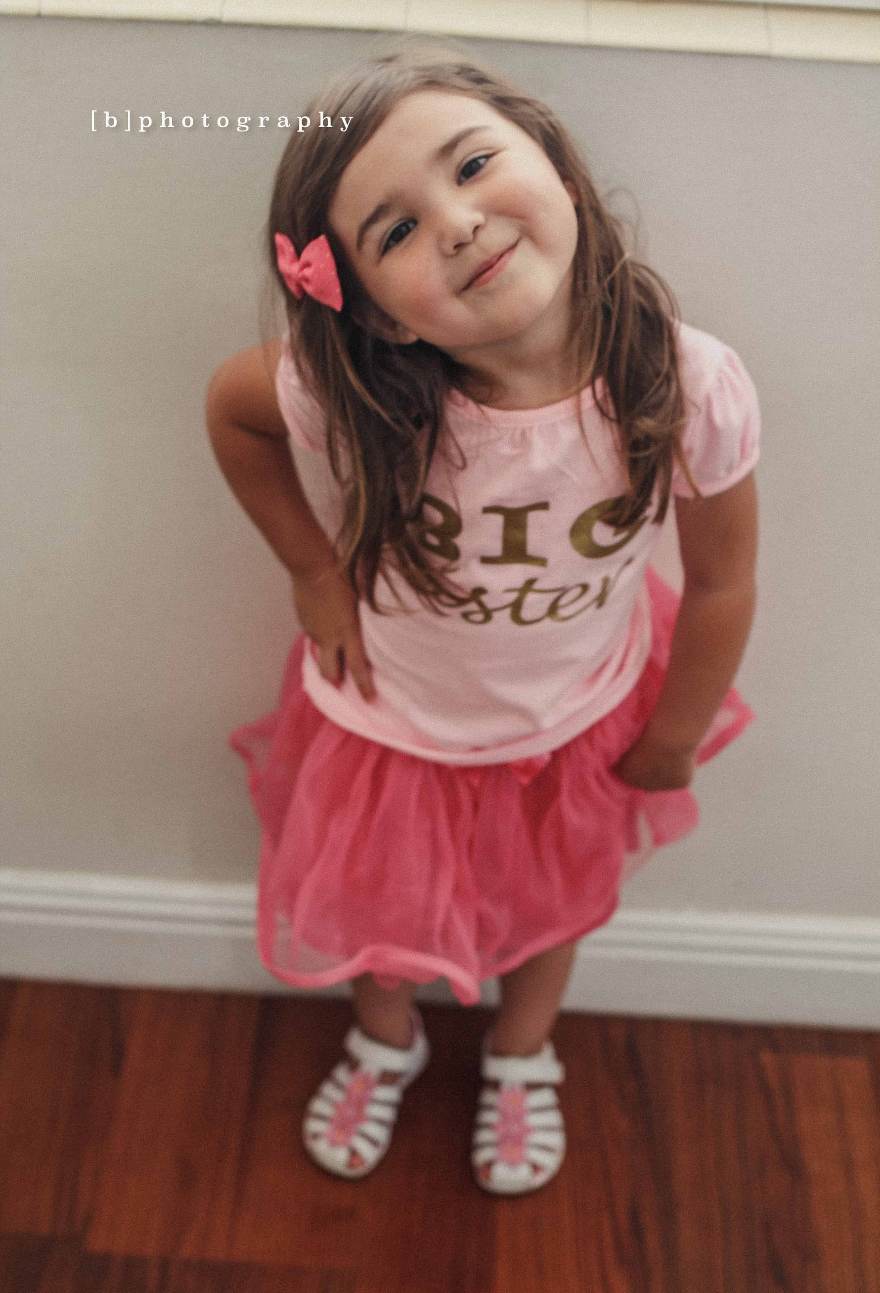 Smiling Girl with a bow in her head wearing all pink with a hand on her hip