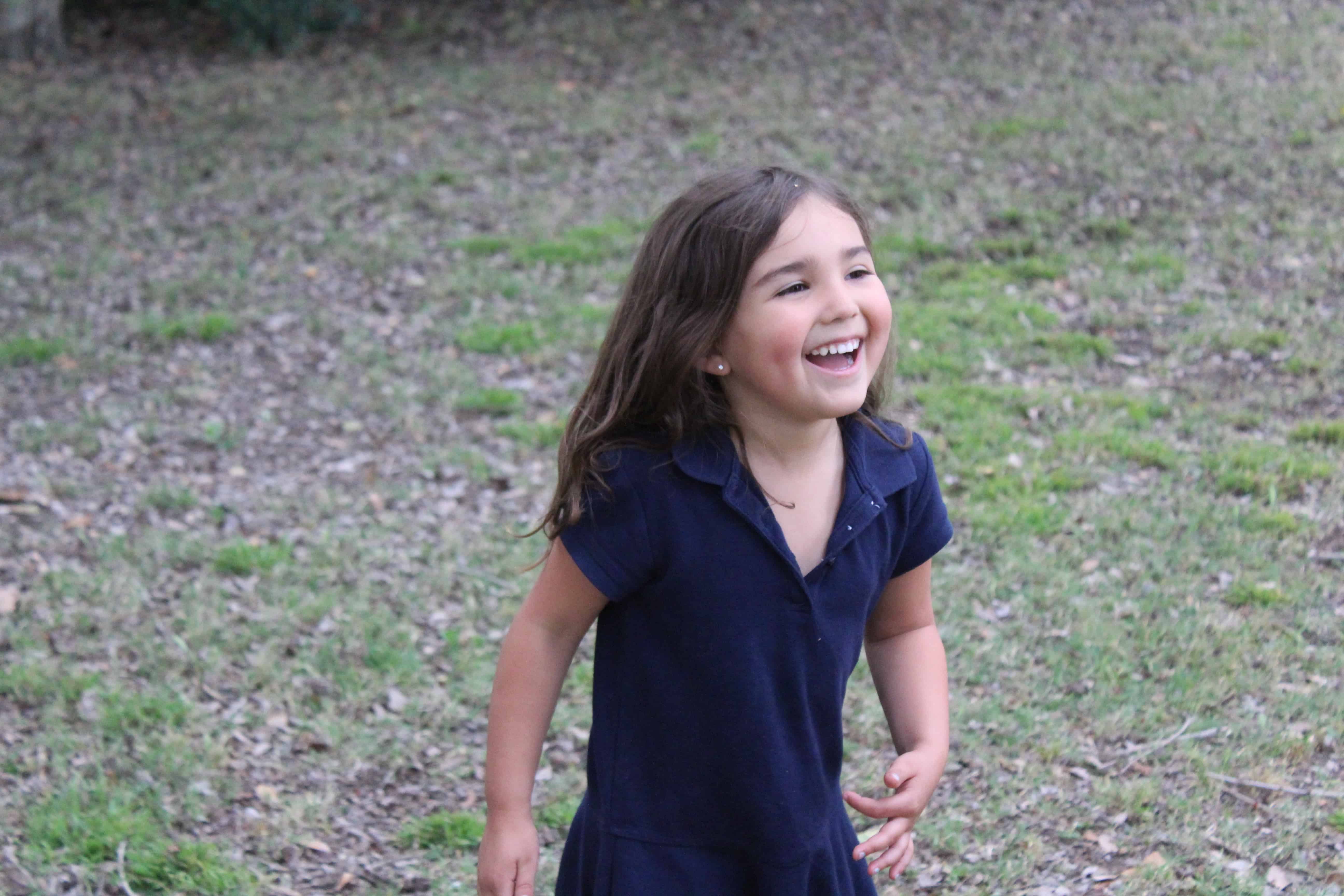 Little girl walking outside a big smile on her face while she plays