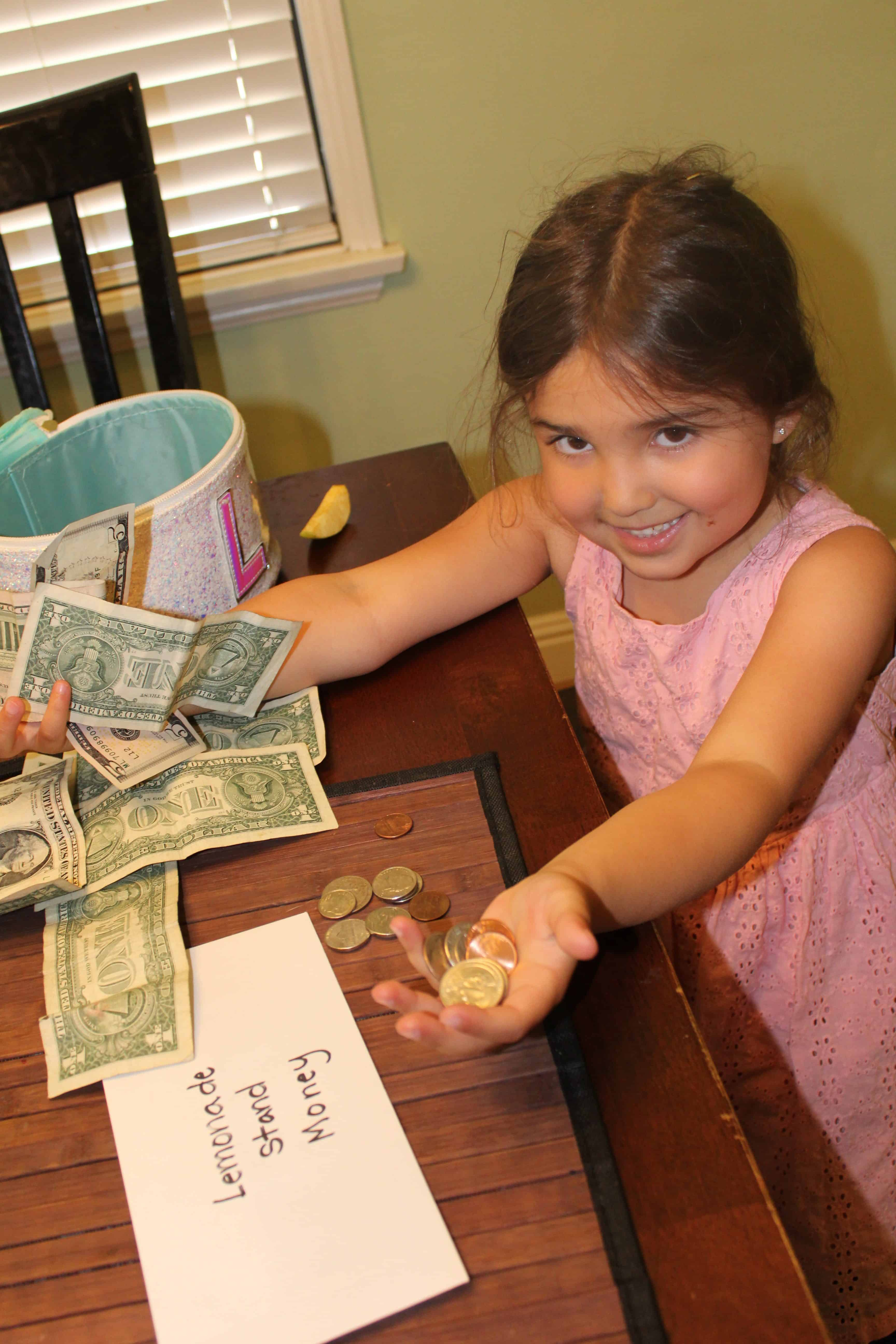 A little girl holding out Quarters and Dimes