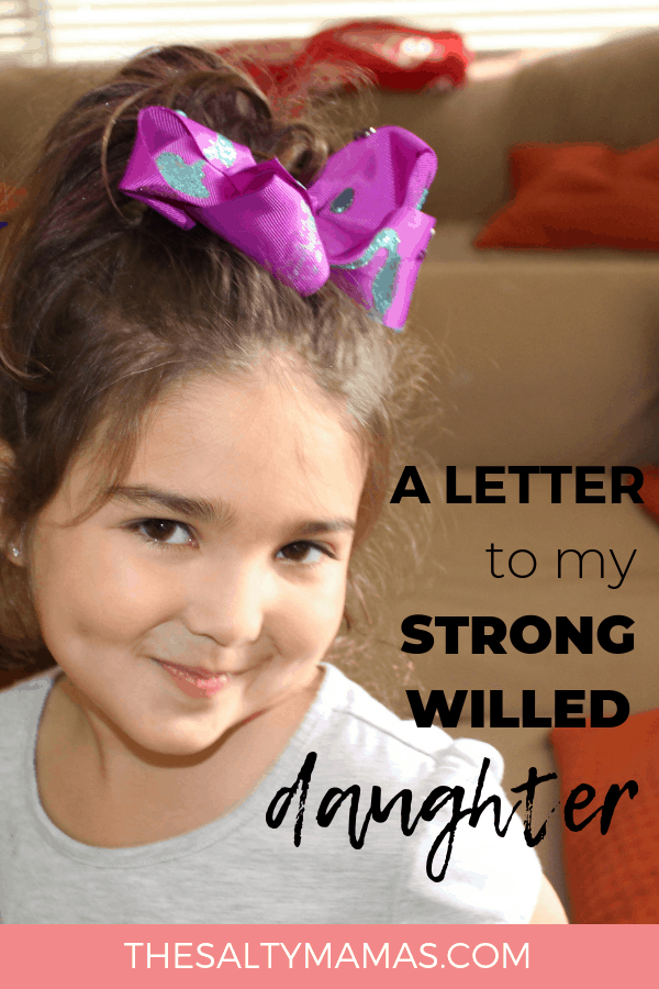 Smiling Girl with a bow in her head. Text overlay: A letter to my strong willed daughter.
