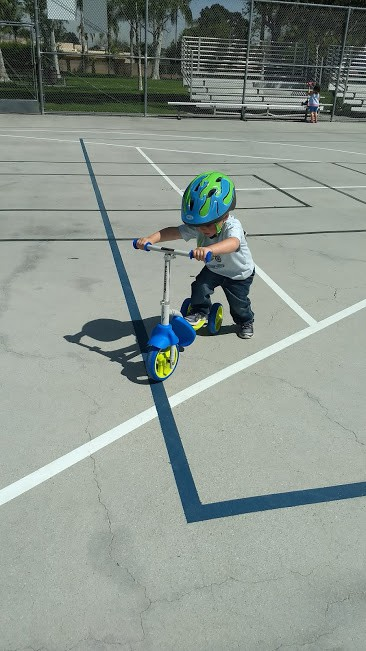 three year old riding a scooter