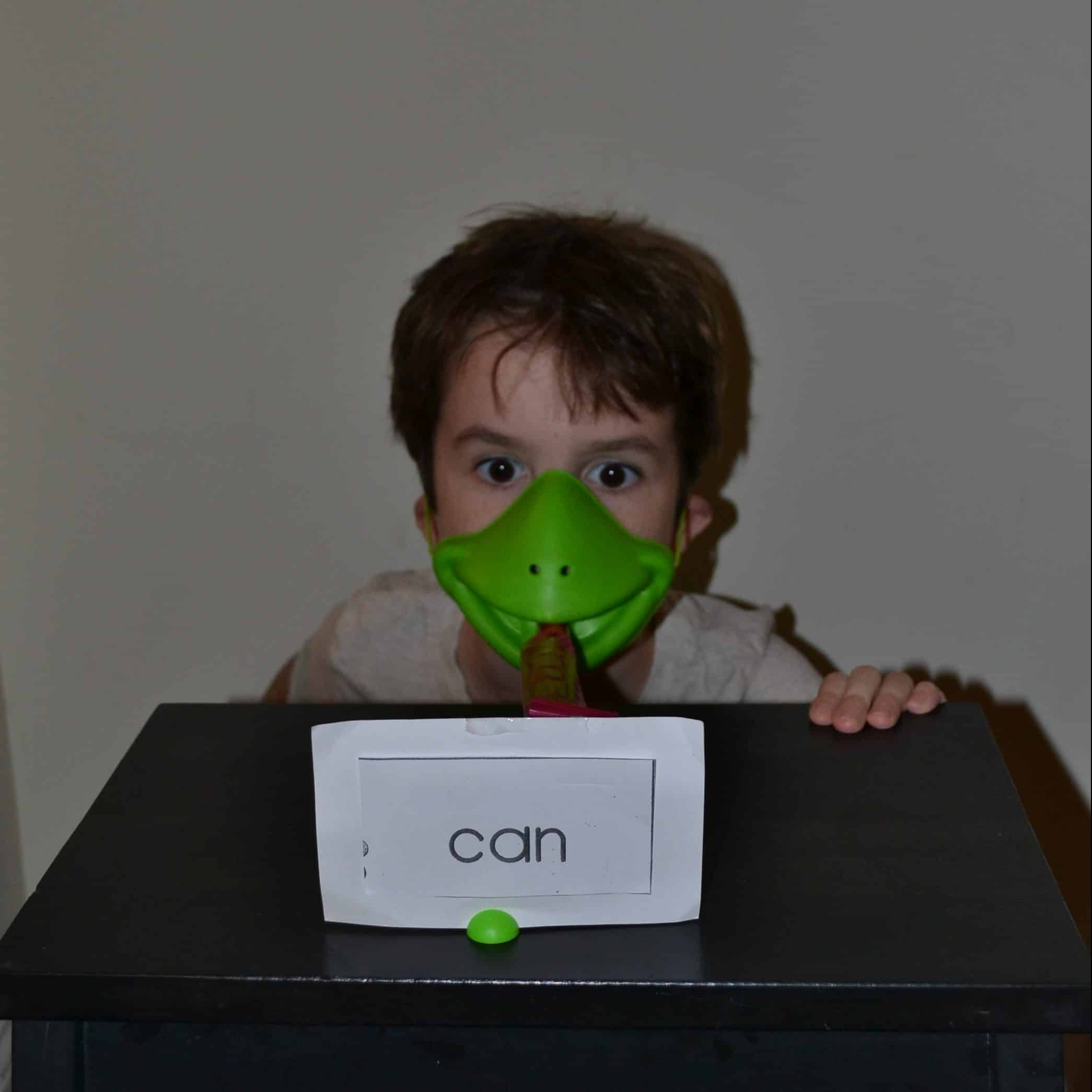 child wearing frog mask to practice sight words