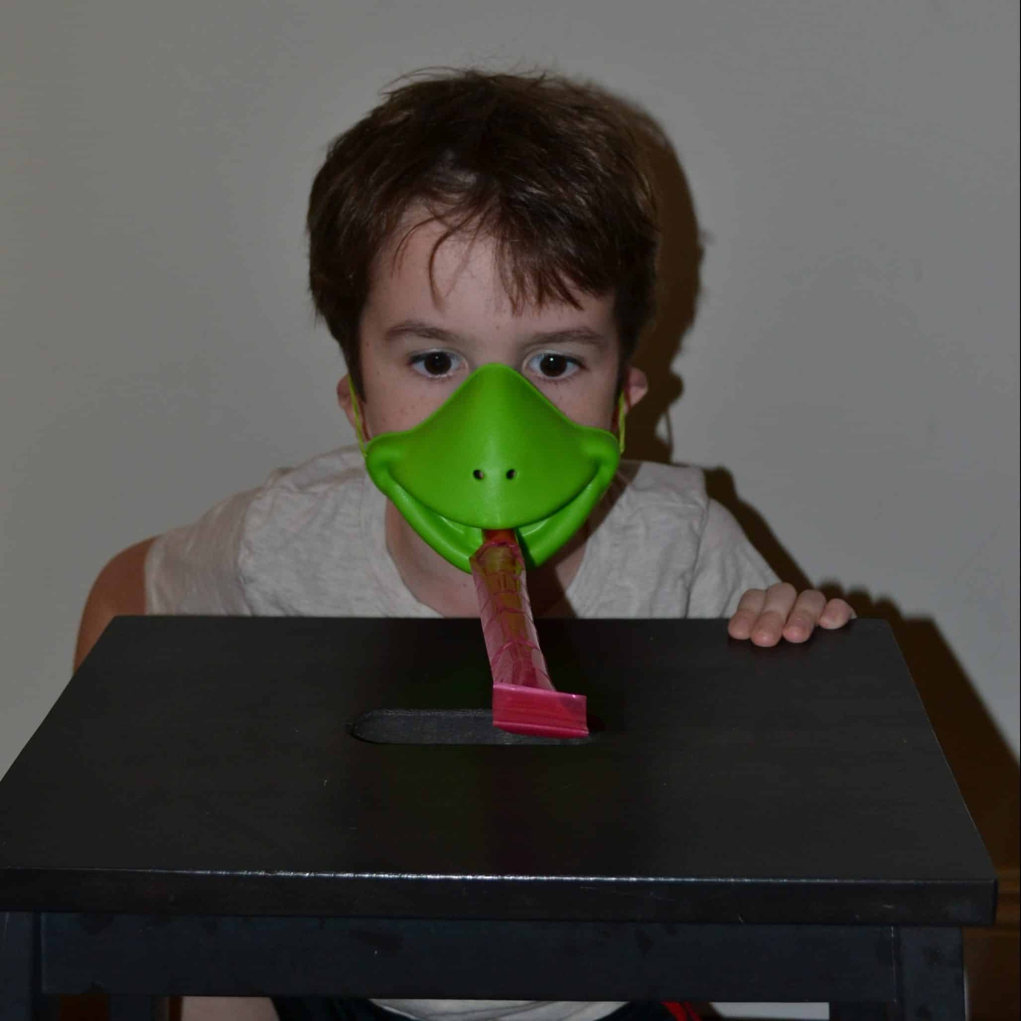 child wearing tic tac frog mask