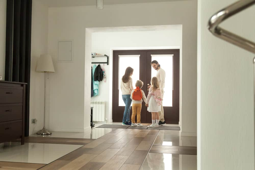 Family standing at the front door getting ready to leave