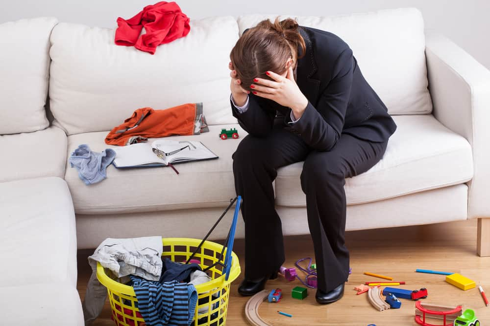 Frustrated woman with head in hands on a couch with clothes and toys spread around.