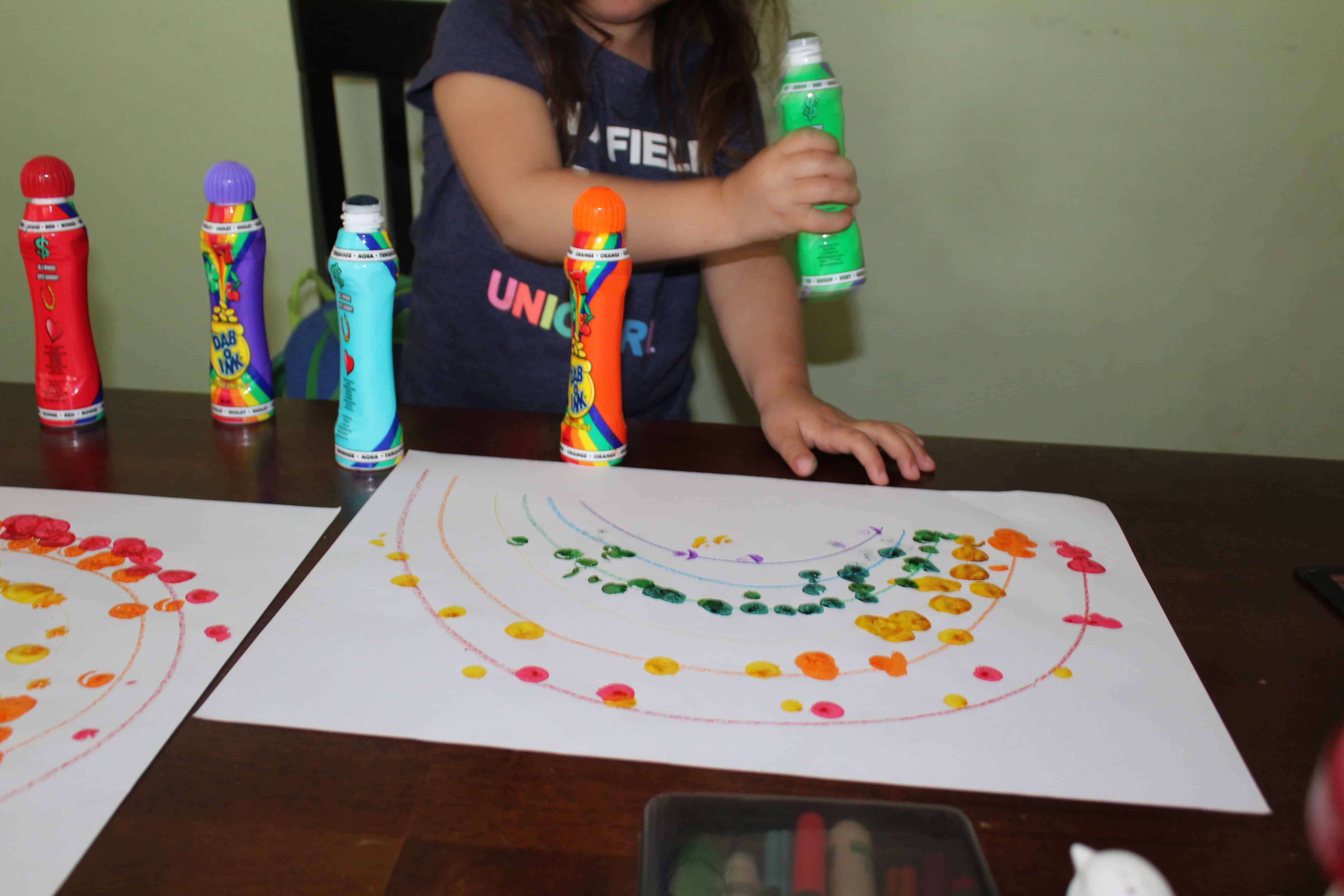 toddler making a rainbow with do a dot markers