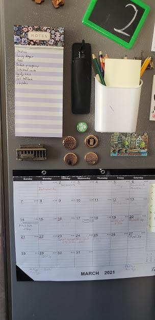 a calendar and tools on a fridge