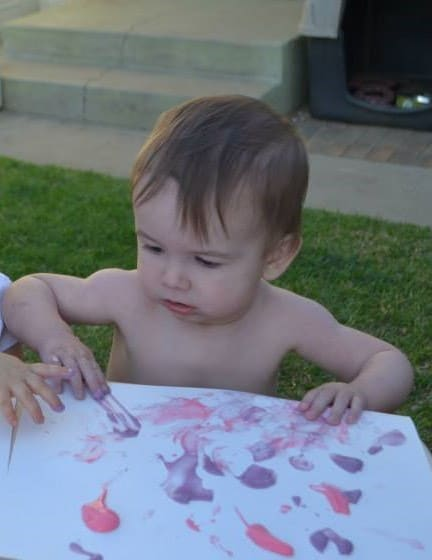 Toddler painting outside with a paintbrush