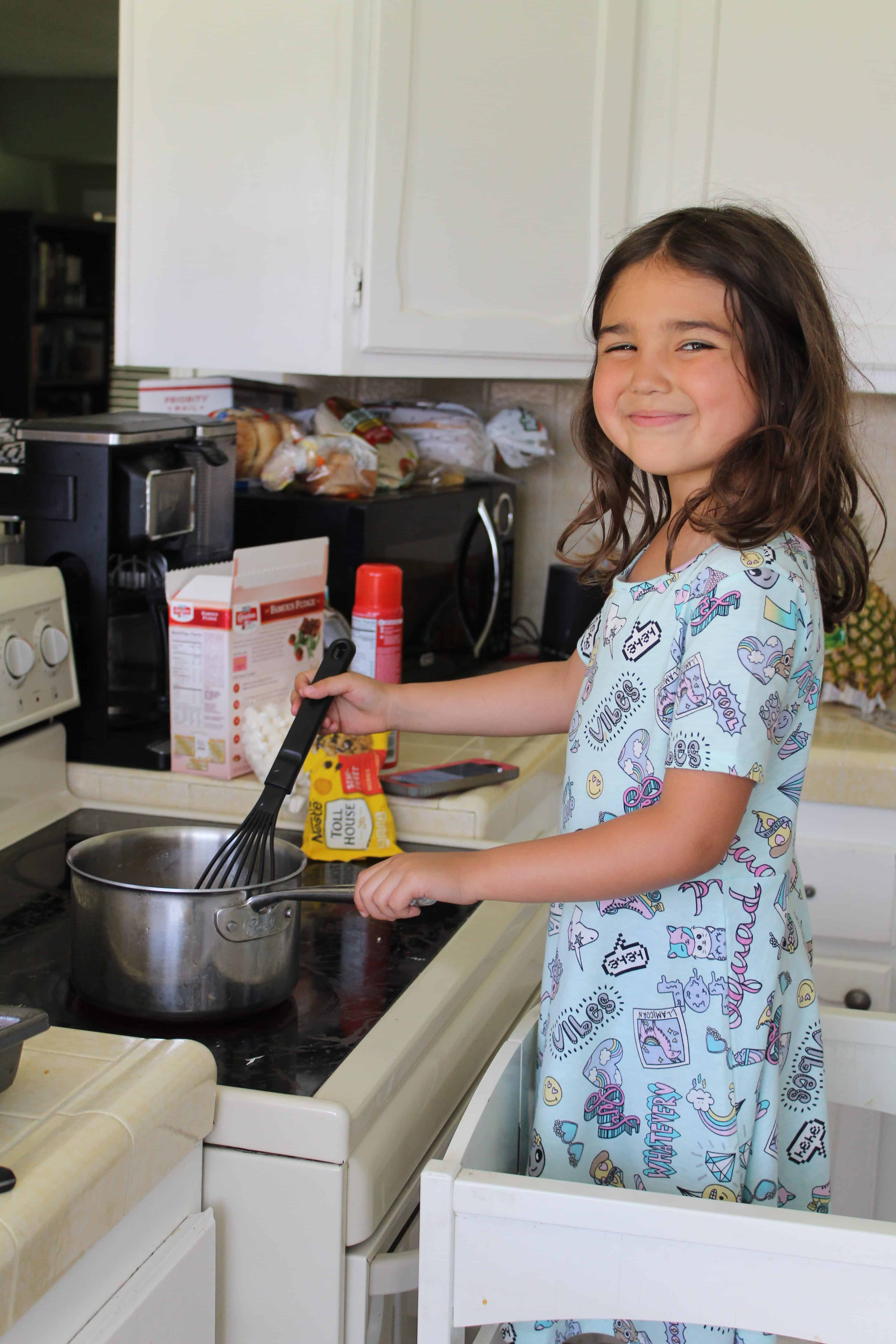 Child helping with the dinner meal mixing on the stove.