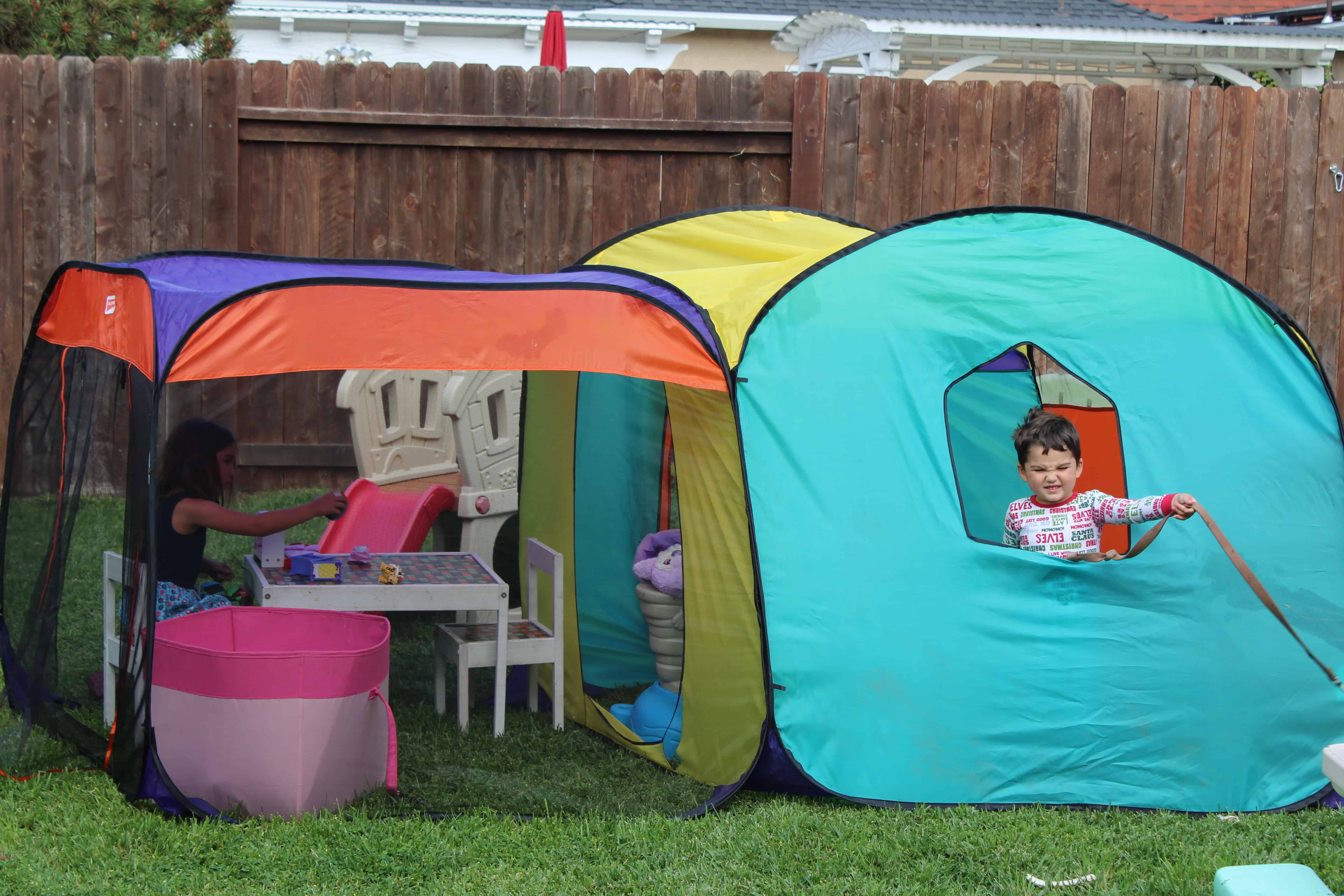Two kids playing with their cool toys(forts) in the backyard.