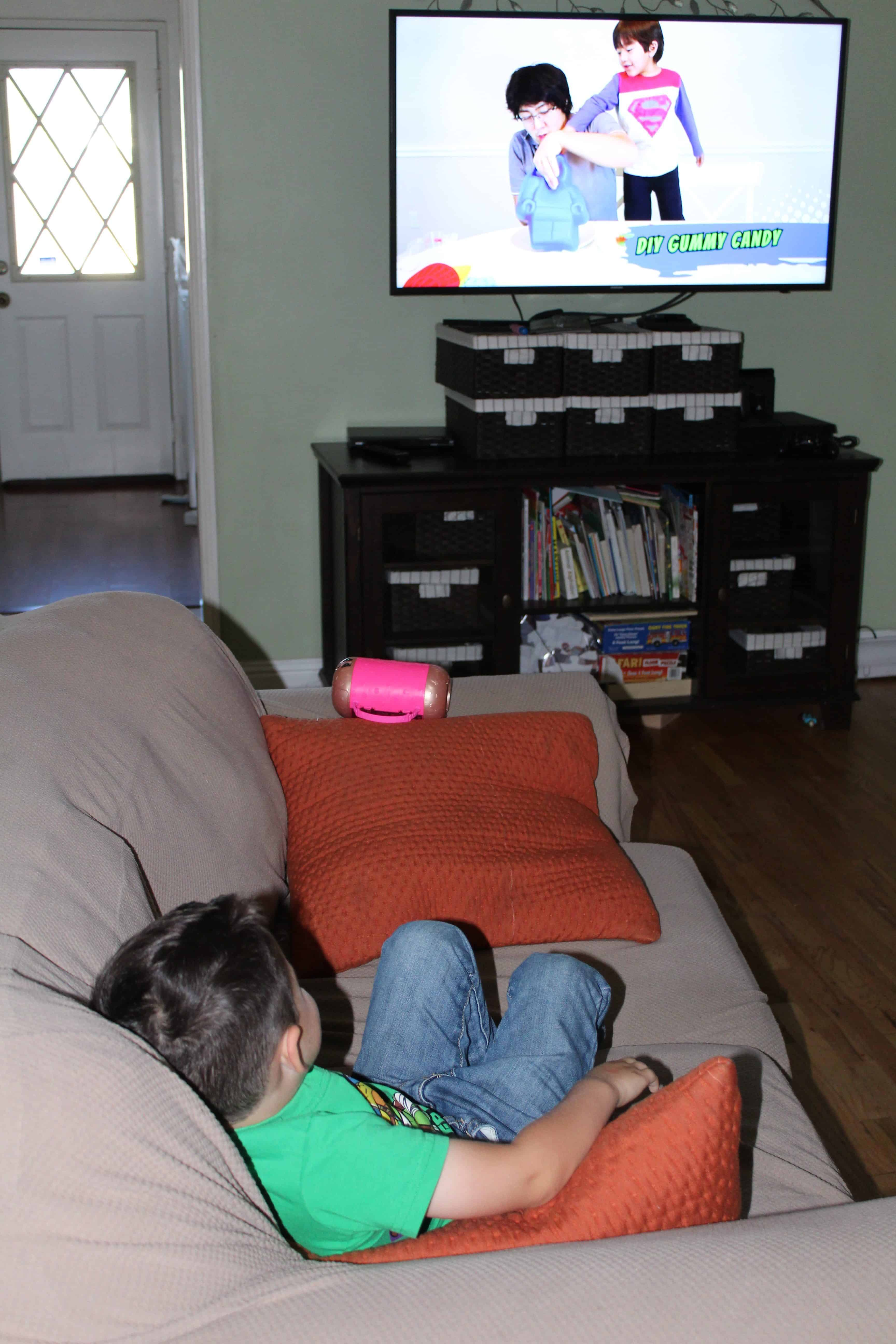 Child sitting on a sofa enjoying screen time on the TV.