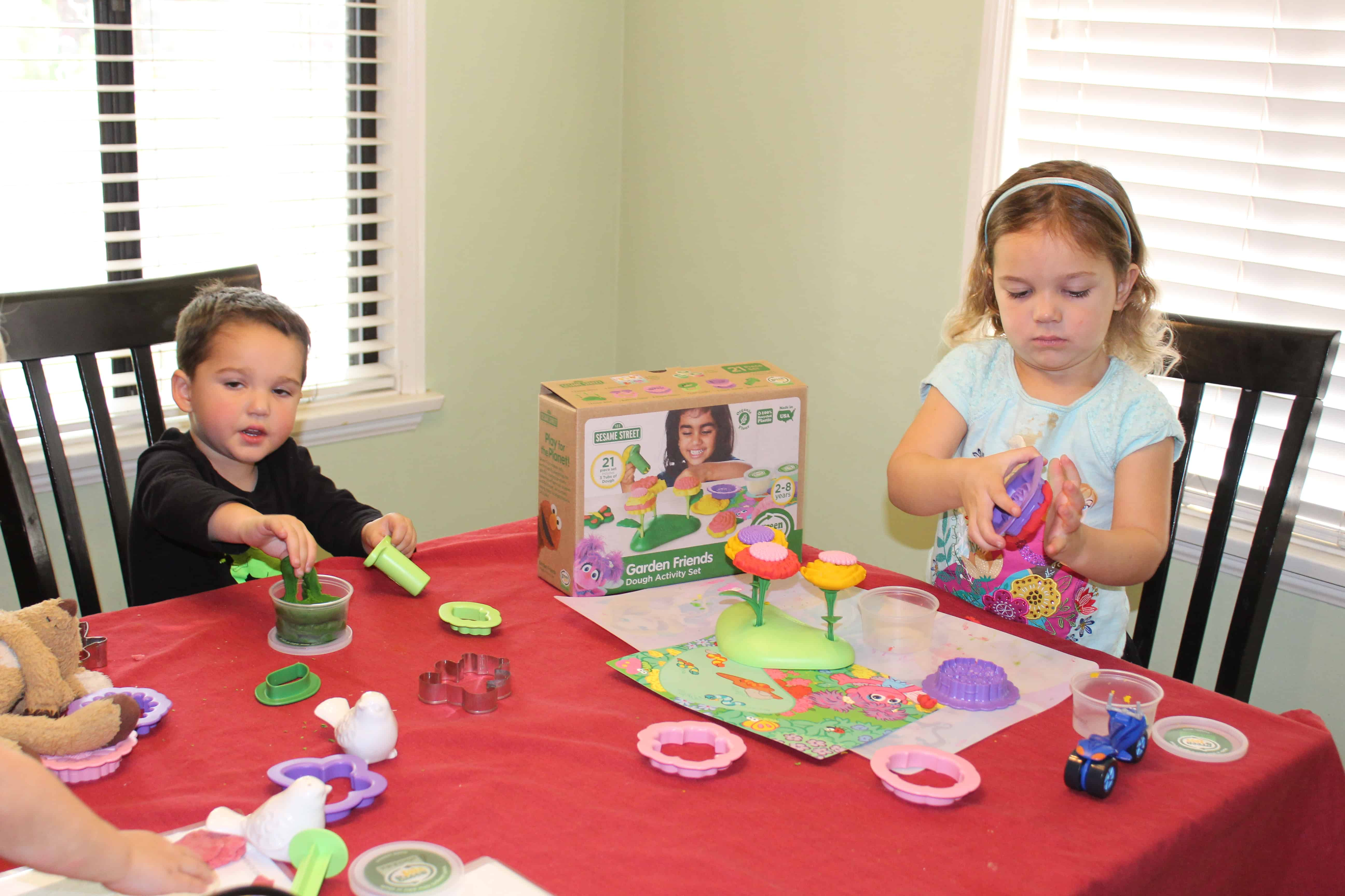 Two toddlers seated at a table playing quietly with play dough