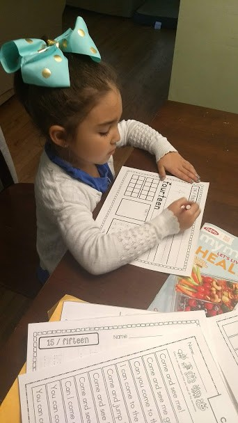 Child sitting at table filling out her nightly homework routine.
